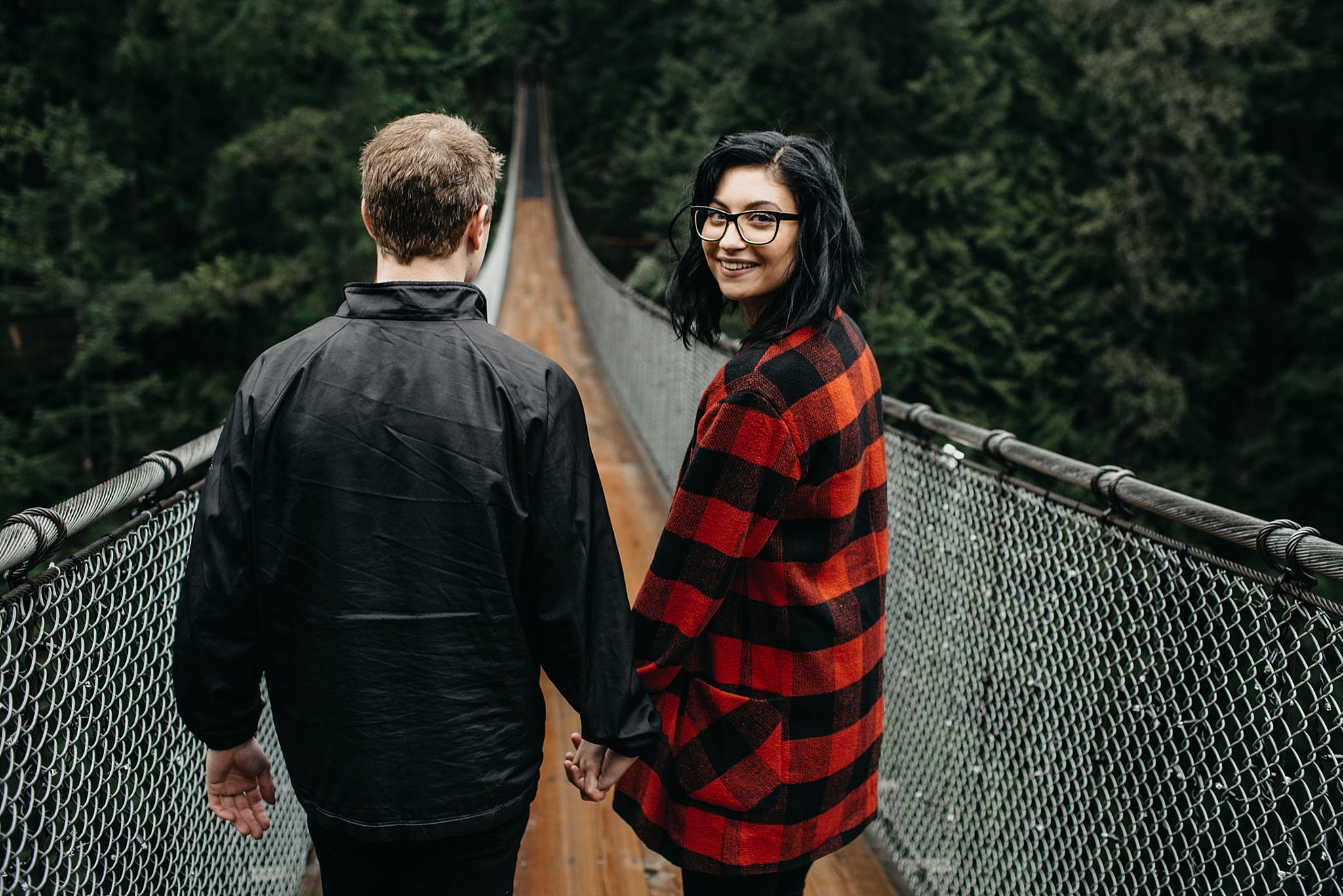 couple walking across capilano suspension bridge engagement photos