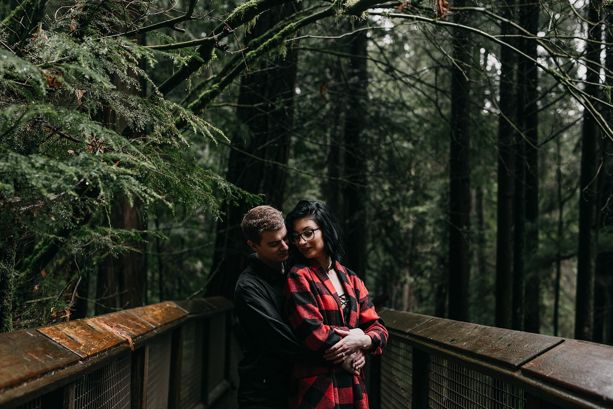 couple hugging on path at capilano suspension bridge for engagement photos