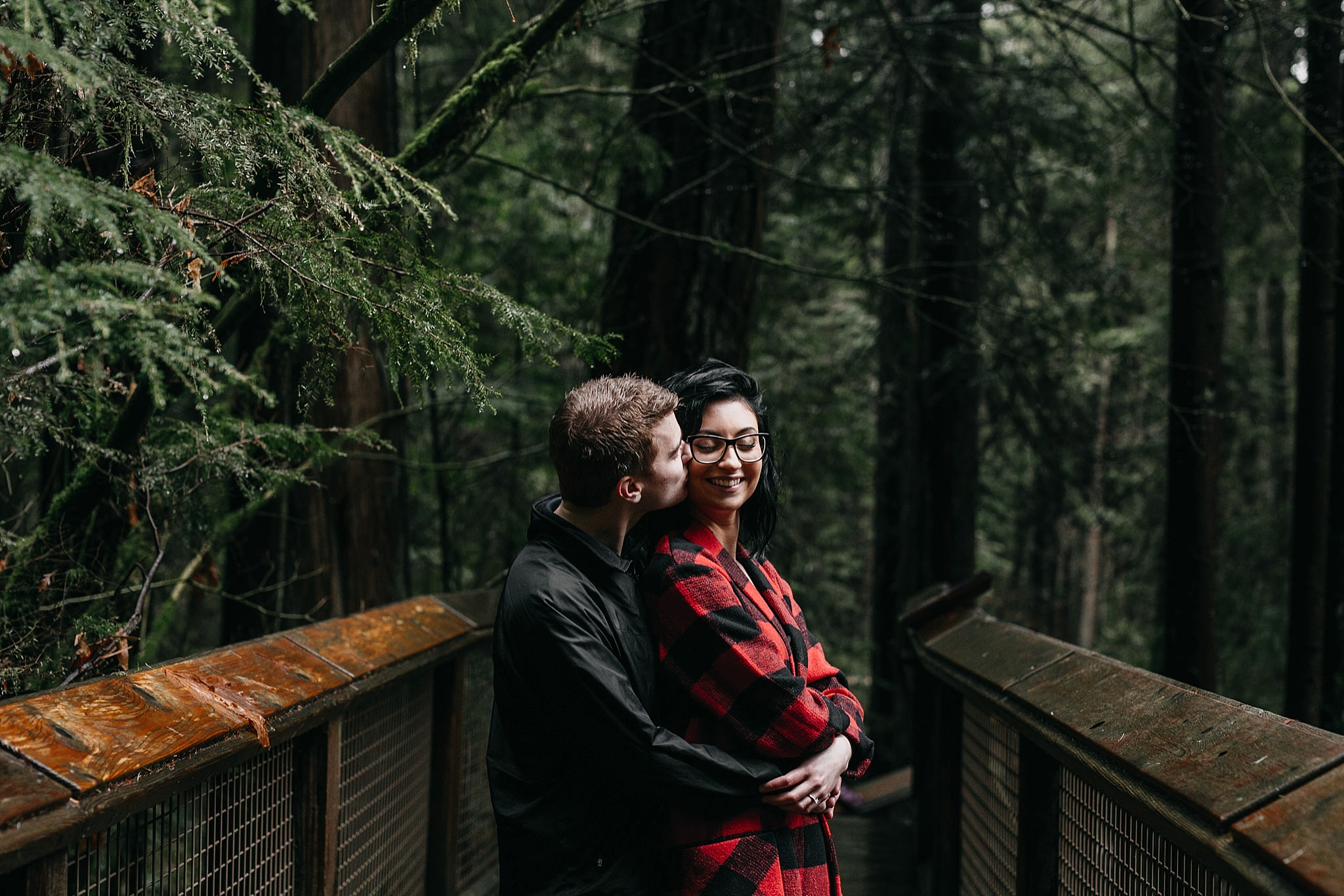 couple kiss on cheek engagement photos capilano suspension bridge north vancouver