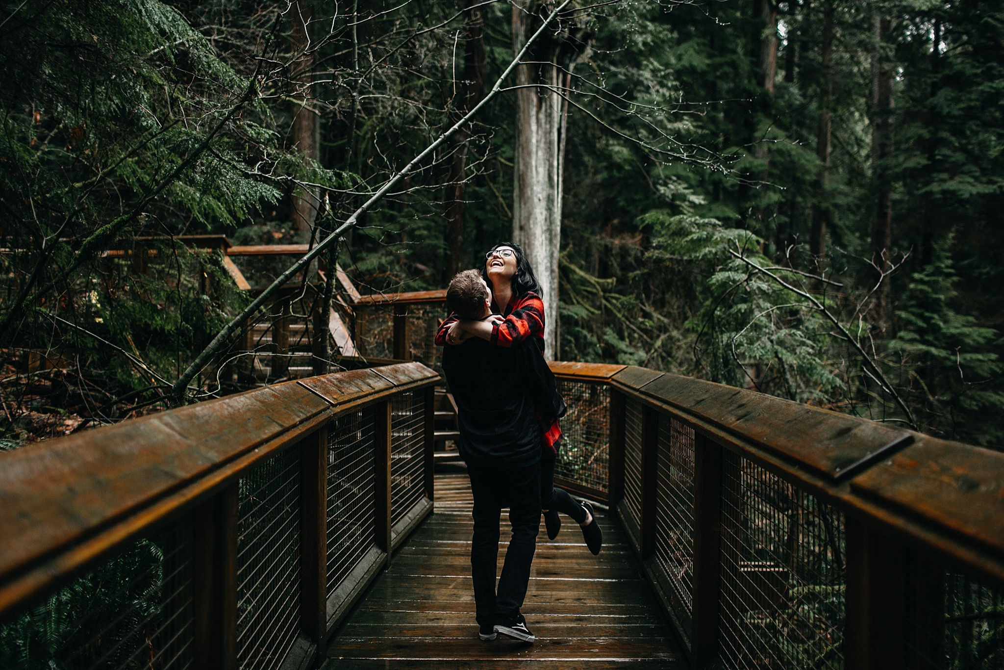 couple guy lifting girl off ground capilano suspension bridge engagement photos