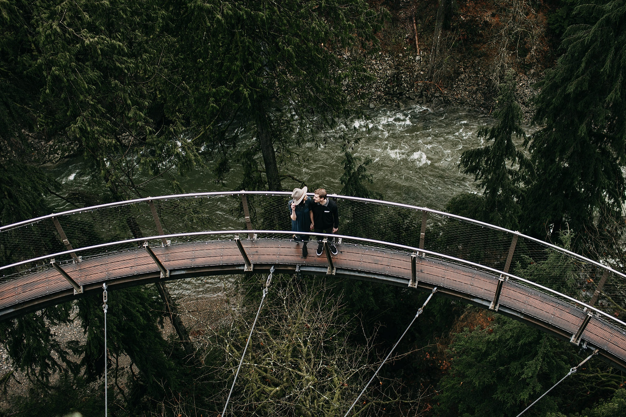 couple walking on cliff walk capilano suspension bridge engagement photos