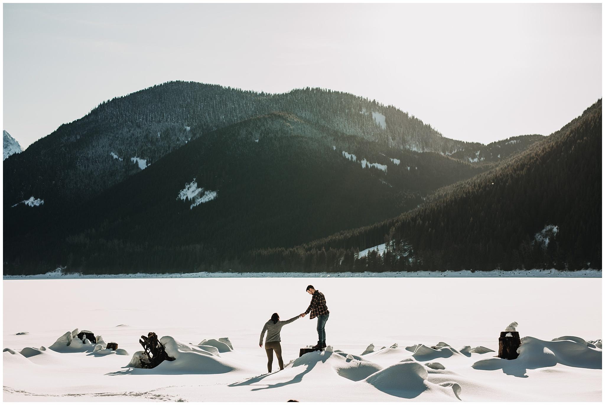 jones lake mountains sun snow couple on tree stump