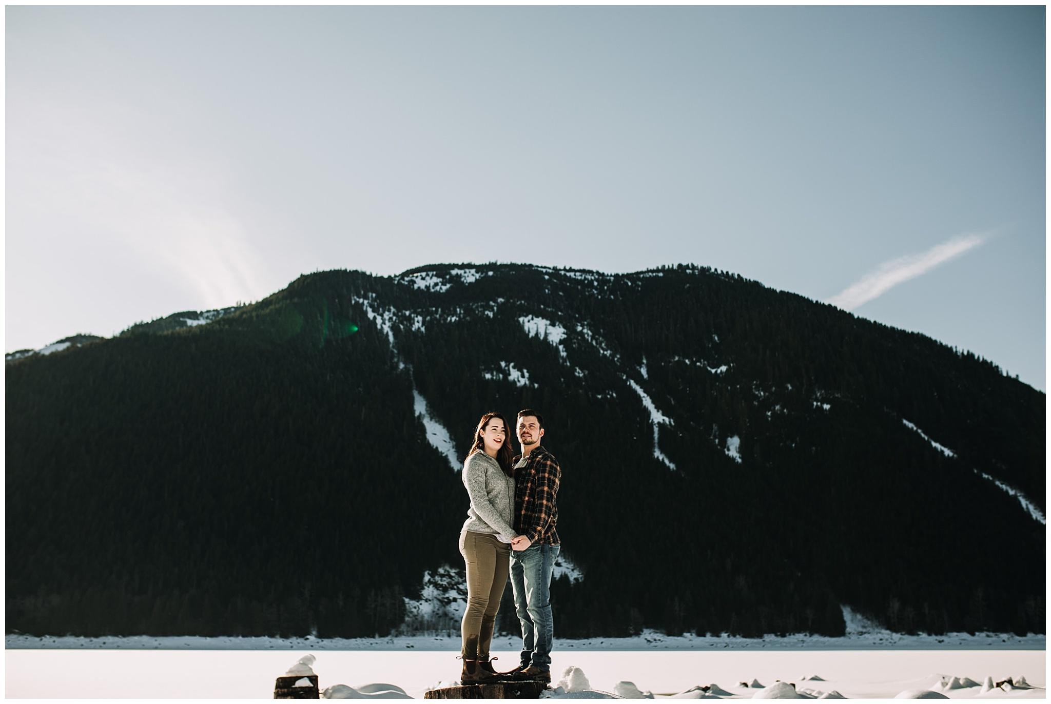 couple standing on tree stump jones lake engagement session