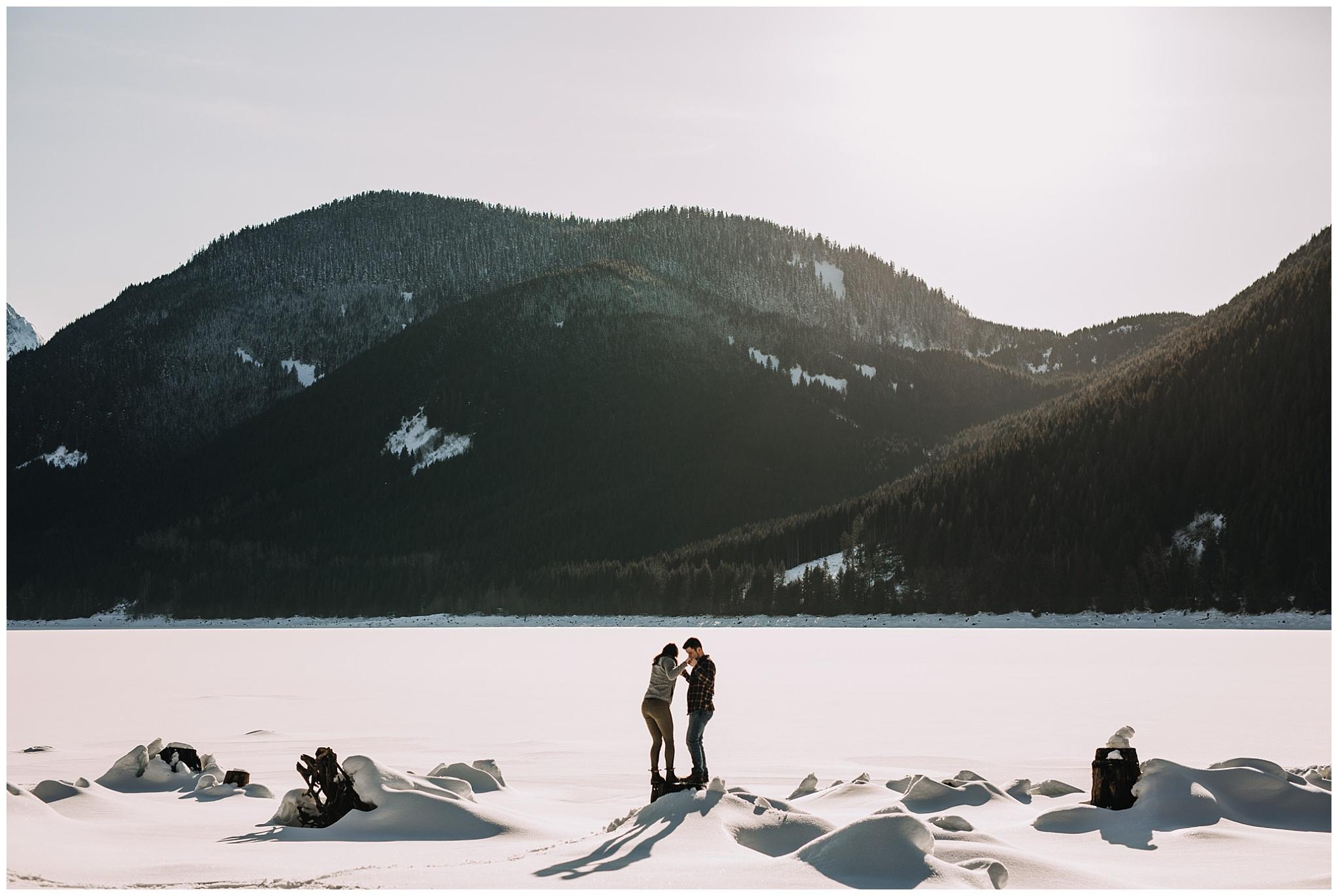 couple on tree stump at jones lake snow mountains sun