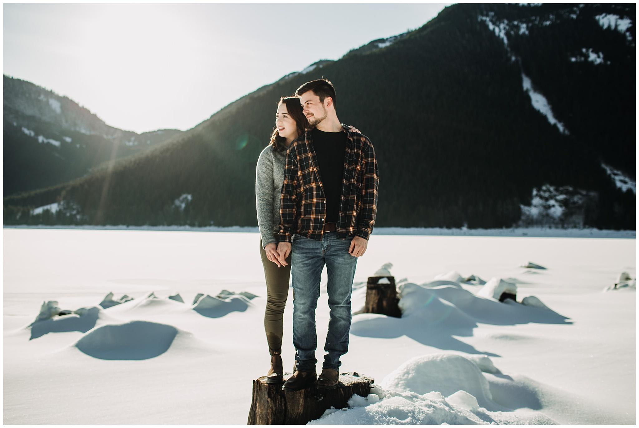couple looking away standing on tree stump jones lake engagement session