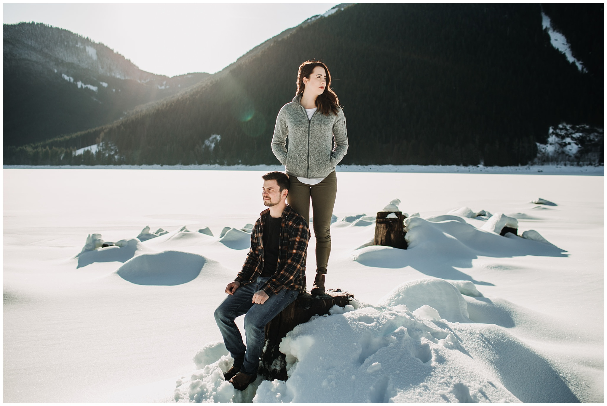 couple sitting and standing on tree stump jones lake snowy engagement session