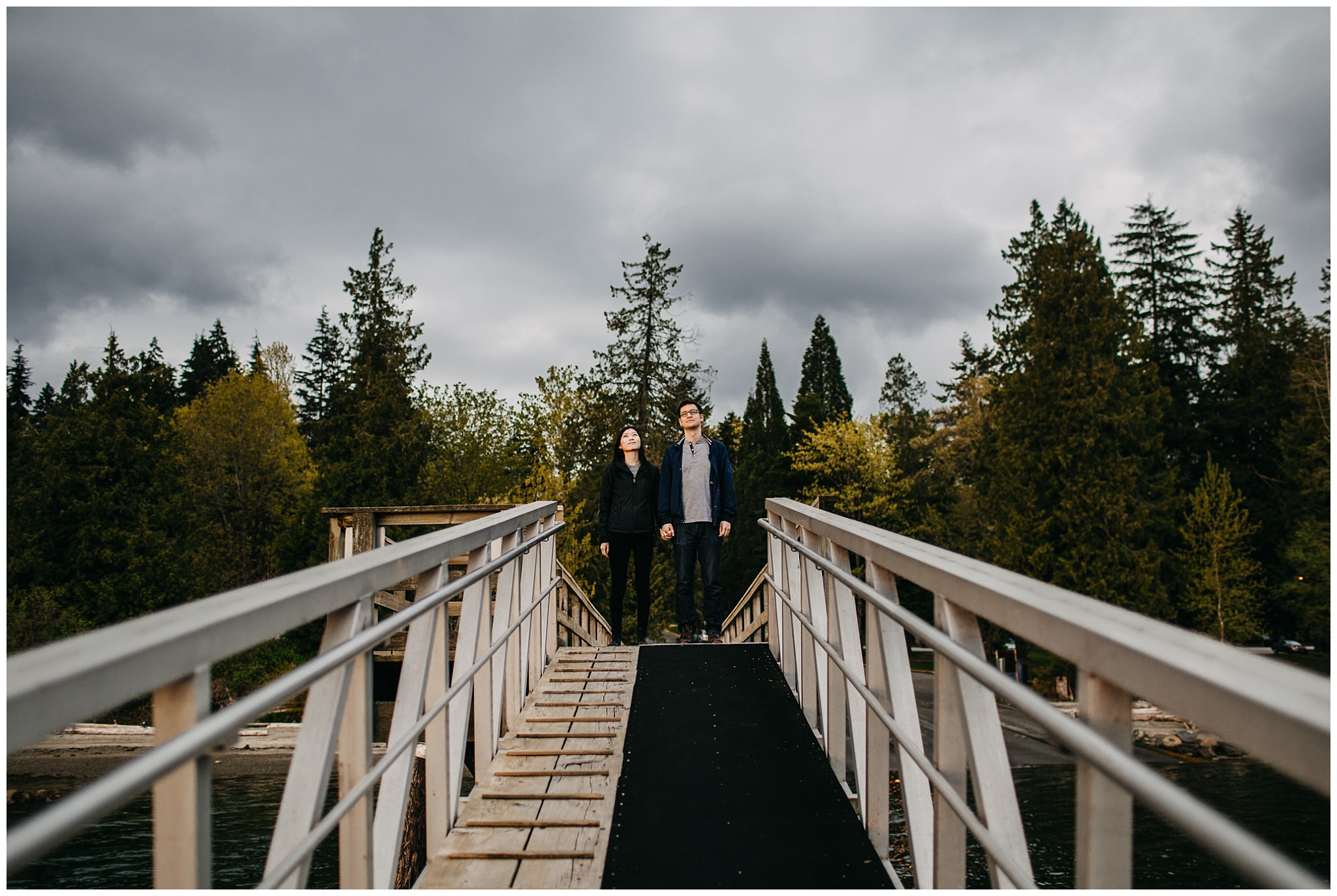 couple dock trees forest moody sky sunset vancouver engagement