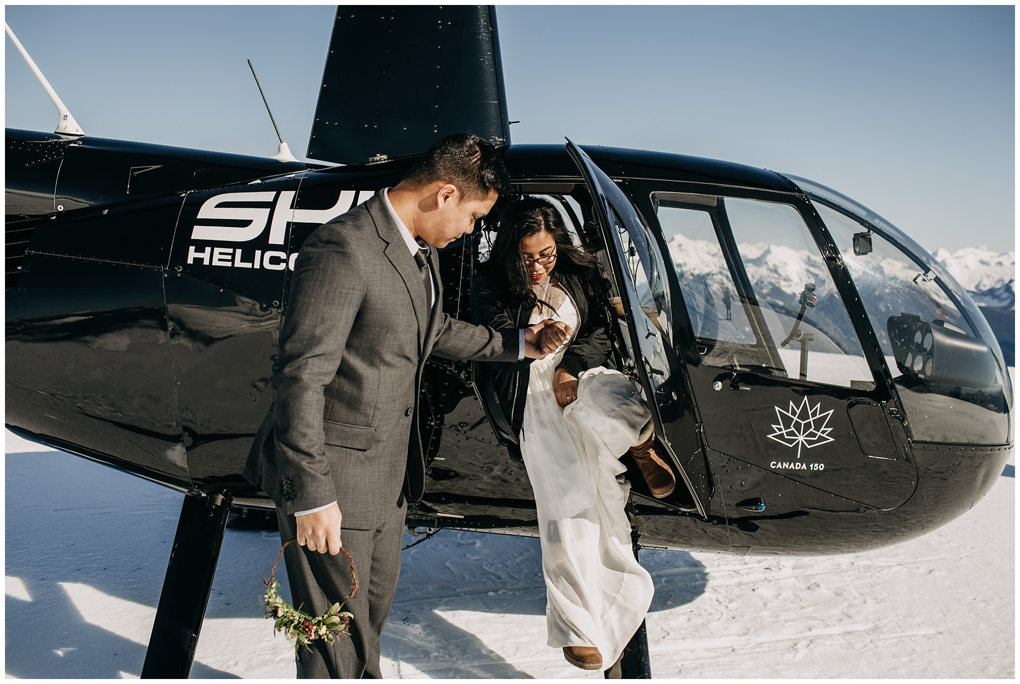 groom helping bride out of helicopter sky helicopters snowy mountaintop wedding portraits