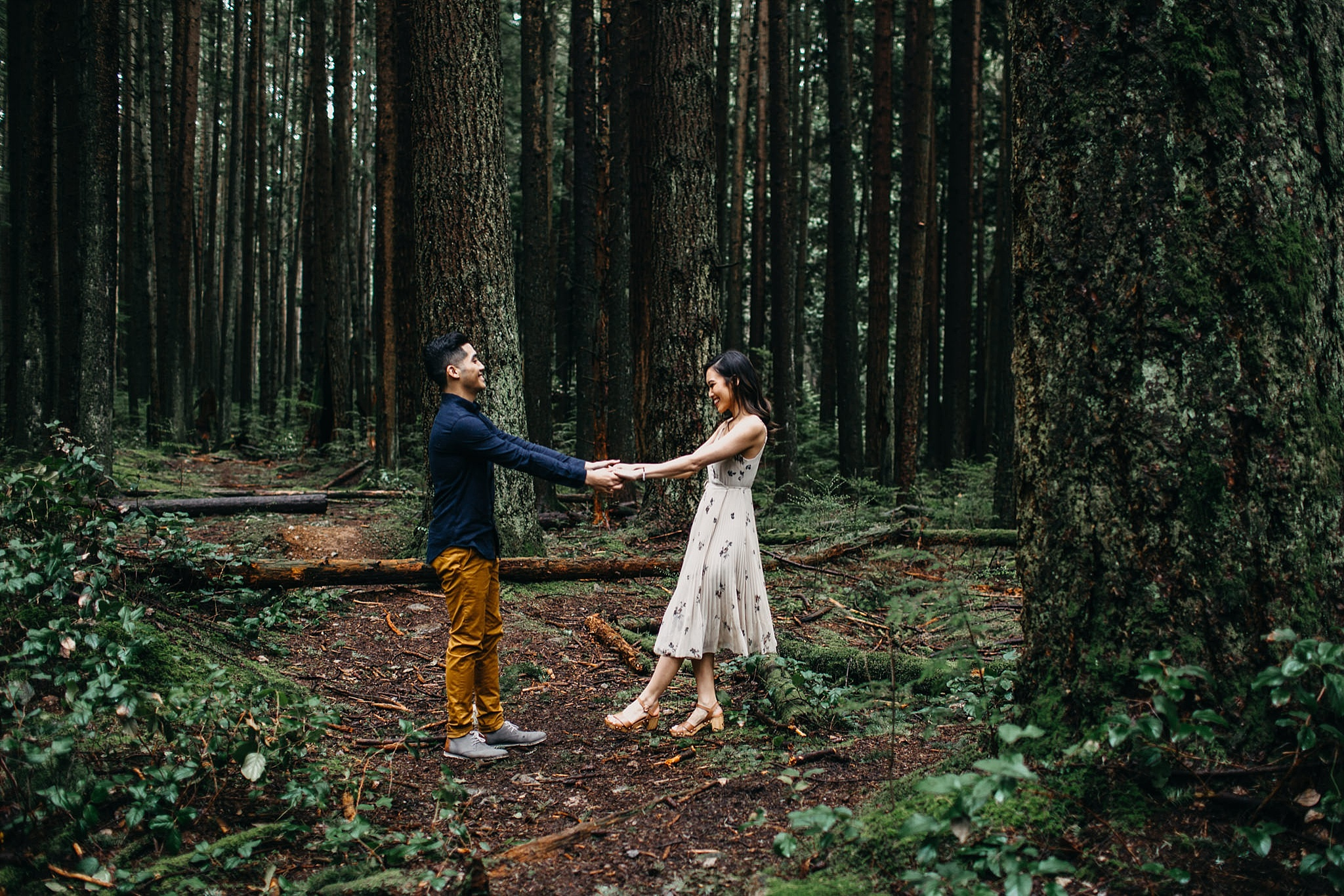 couple dancing in lush forest engagement session vancouver pacific spirit park