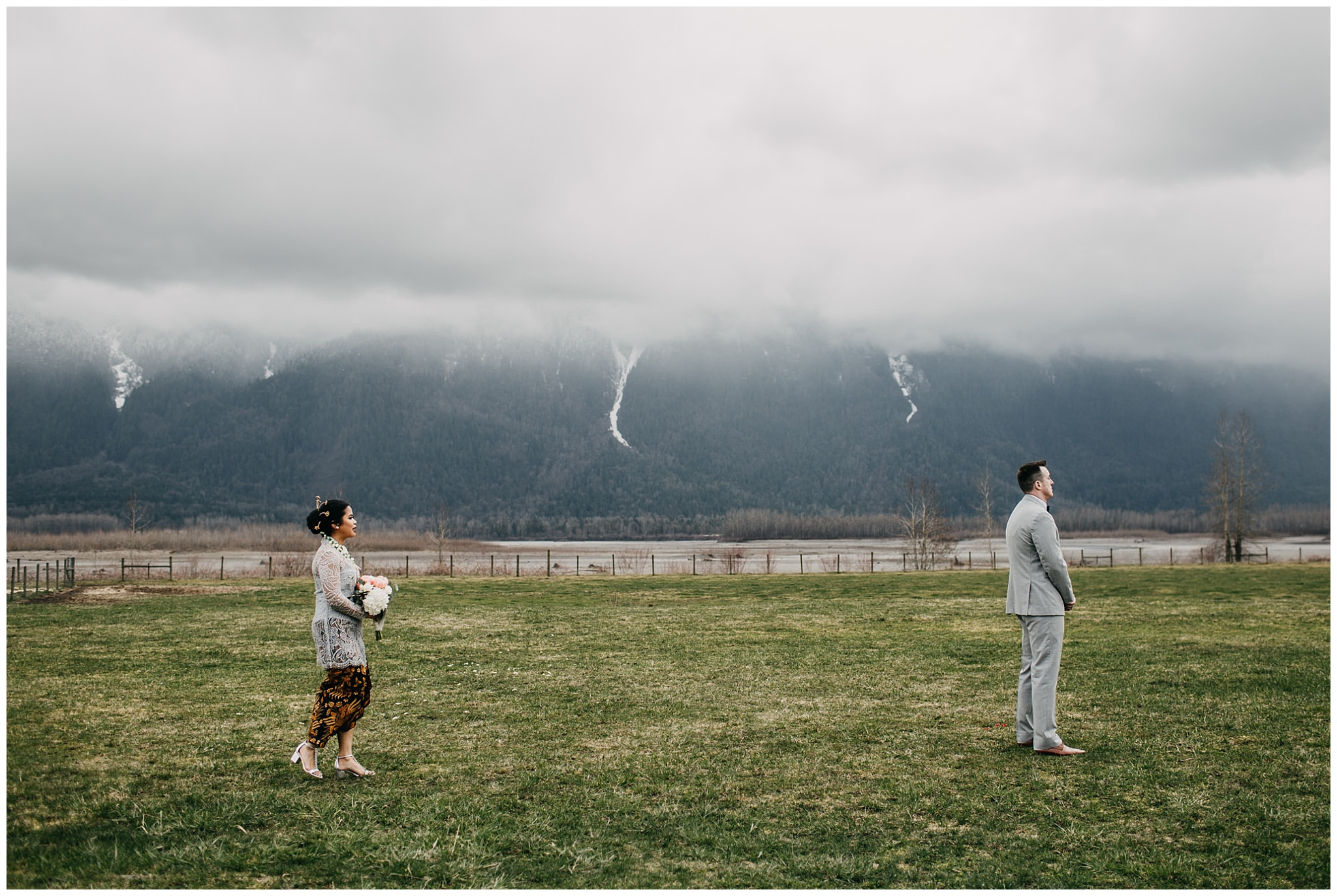 bride and groom first look at fraser river lodge wedding with mountain backdrop