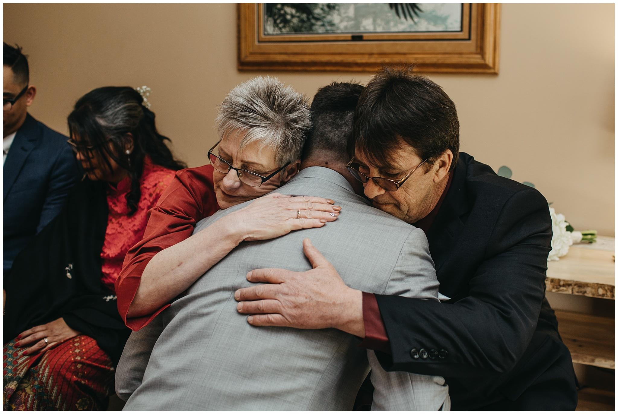 groom hugging parents emotional moment at fraser river lodge wedding