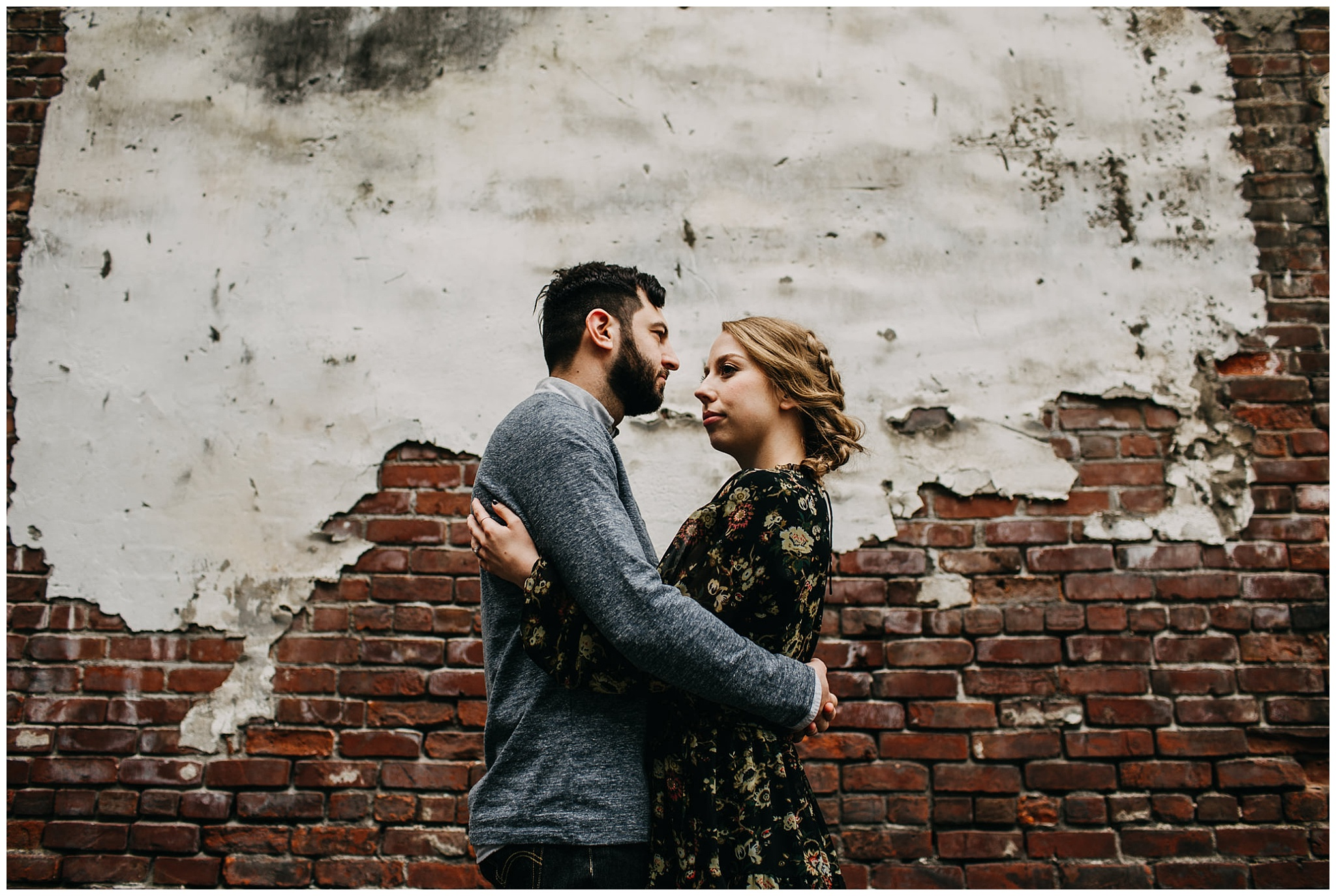 couple in front of brick wall downtown new west urban engagement session