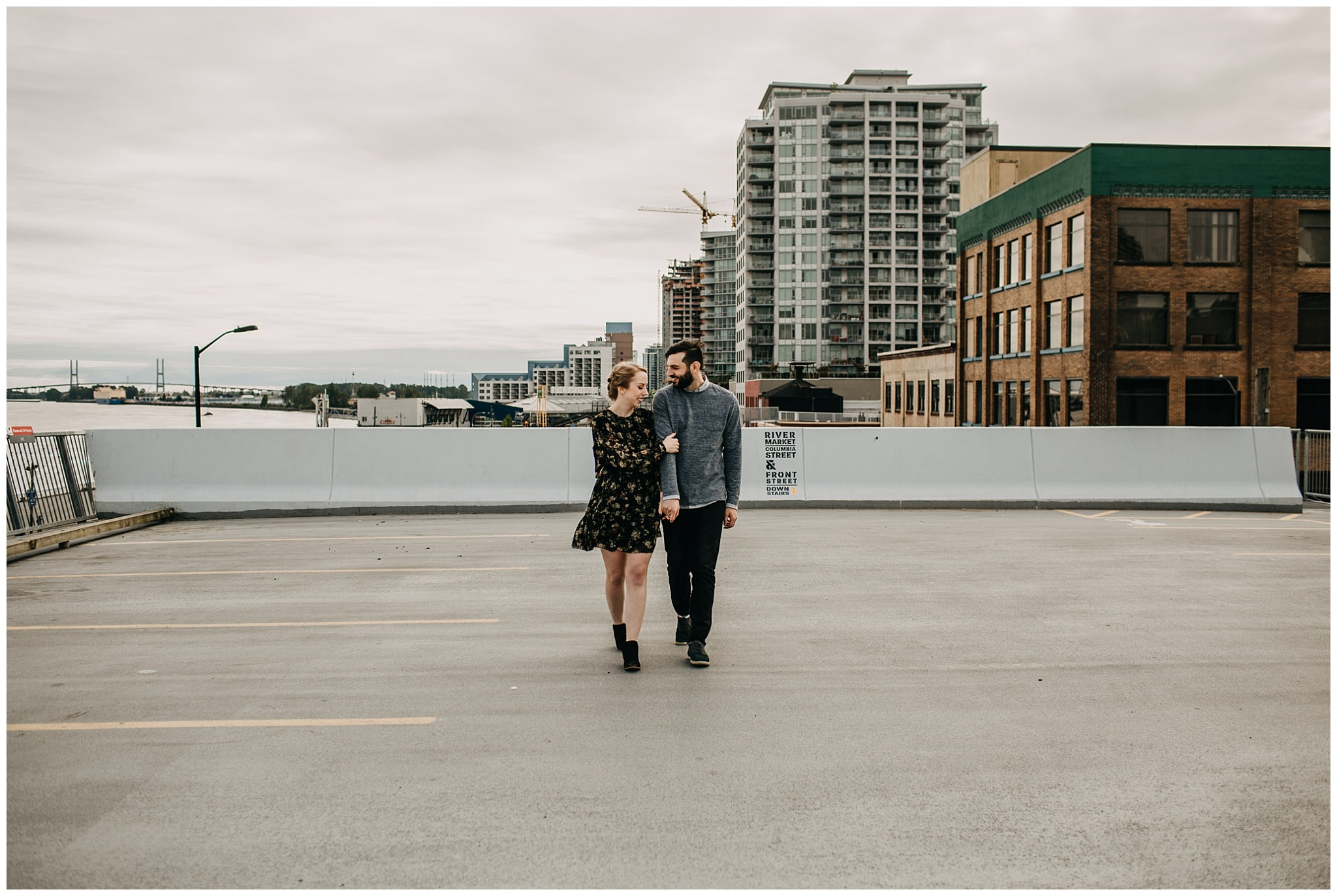 couple walking on rooftop parkade at downtown new west engagement session