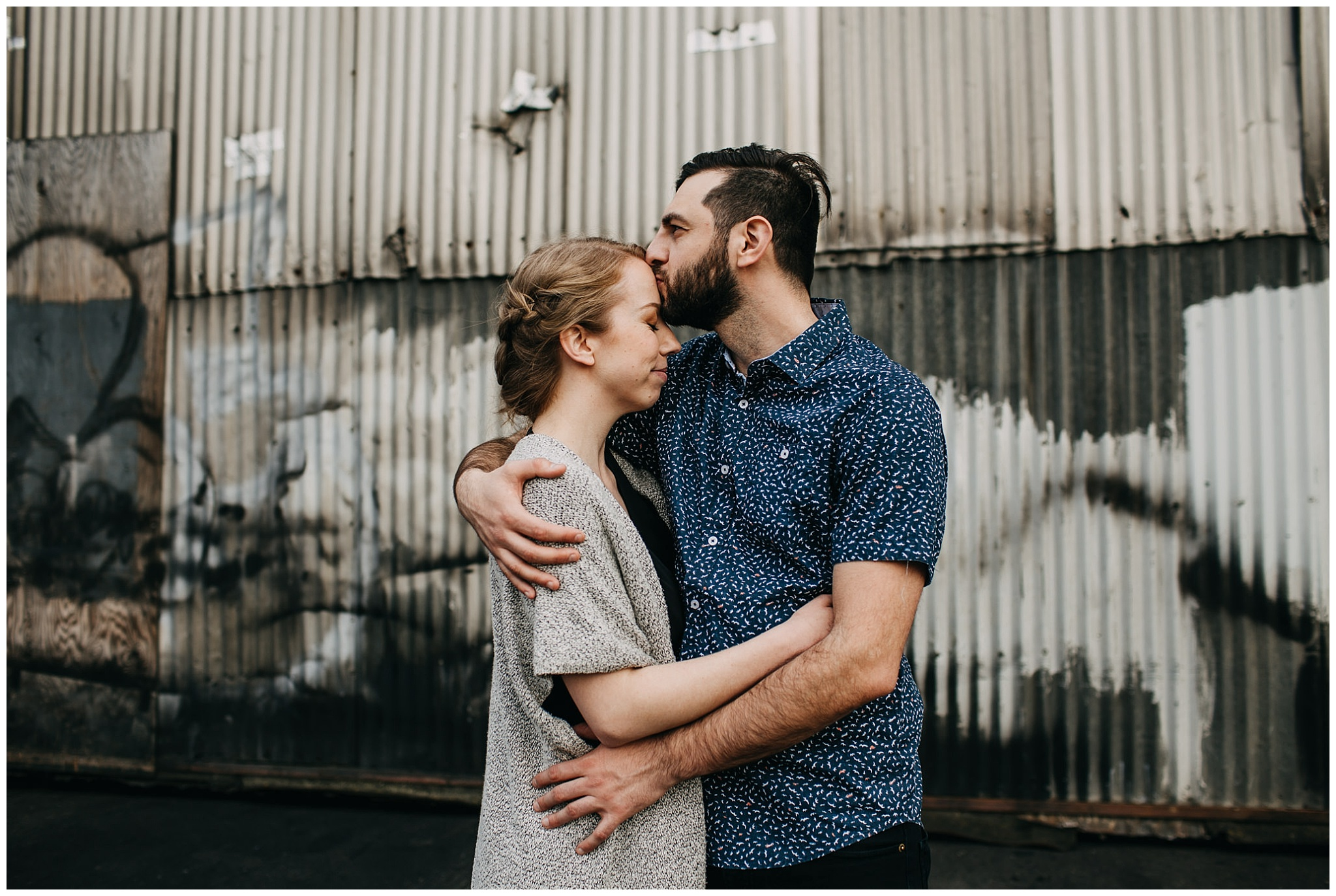 couple hugging in industrial urban setting at downtown new west engagement session