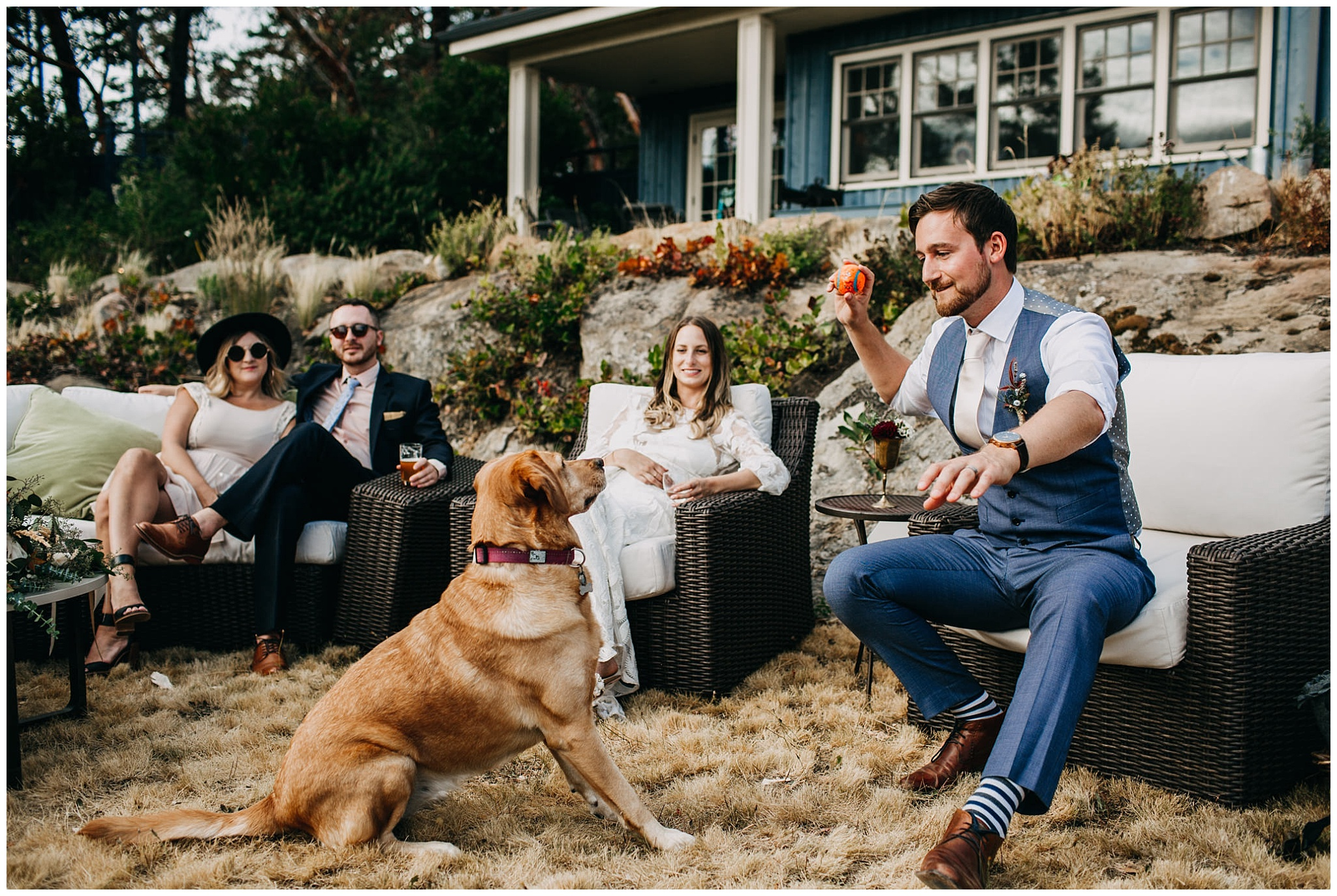 candid moment of groom playing fetch with dog at mayne island wedding
