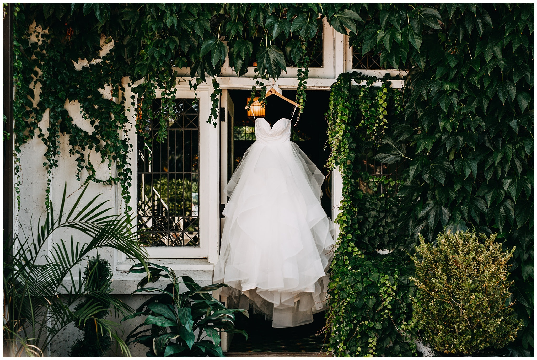 bride's dress hanging in ivy at hycroft manor wedding
