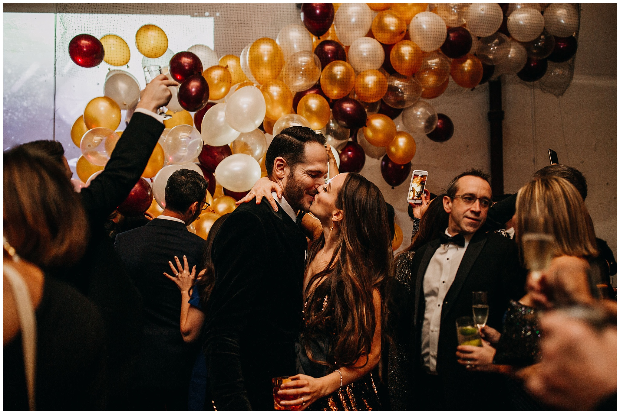 bride and groom new year's kiss with balloon drop at settlement building wedding