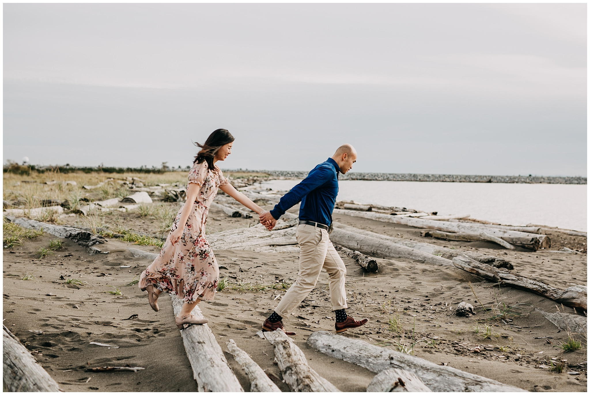 wild couple running on beach at iona beach engagement
