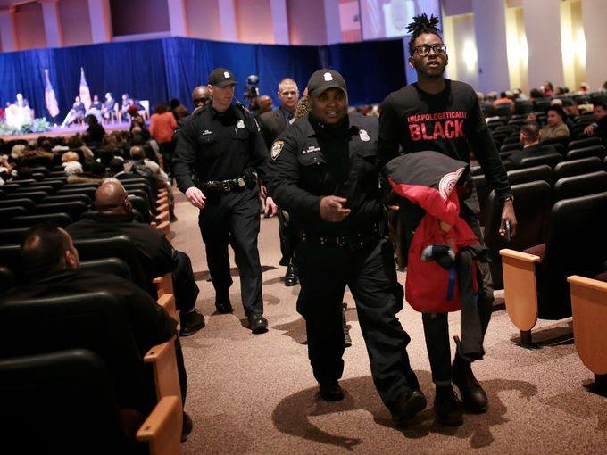 Dakarai Carter being escorted out of the State of the City address after disruption. Photo Credit: Julia Cuneo