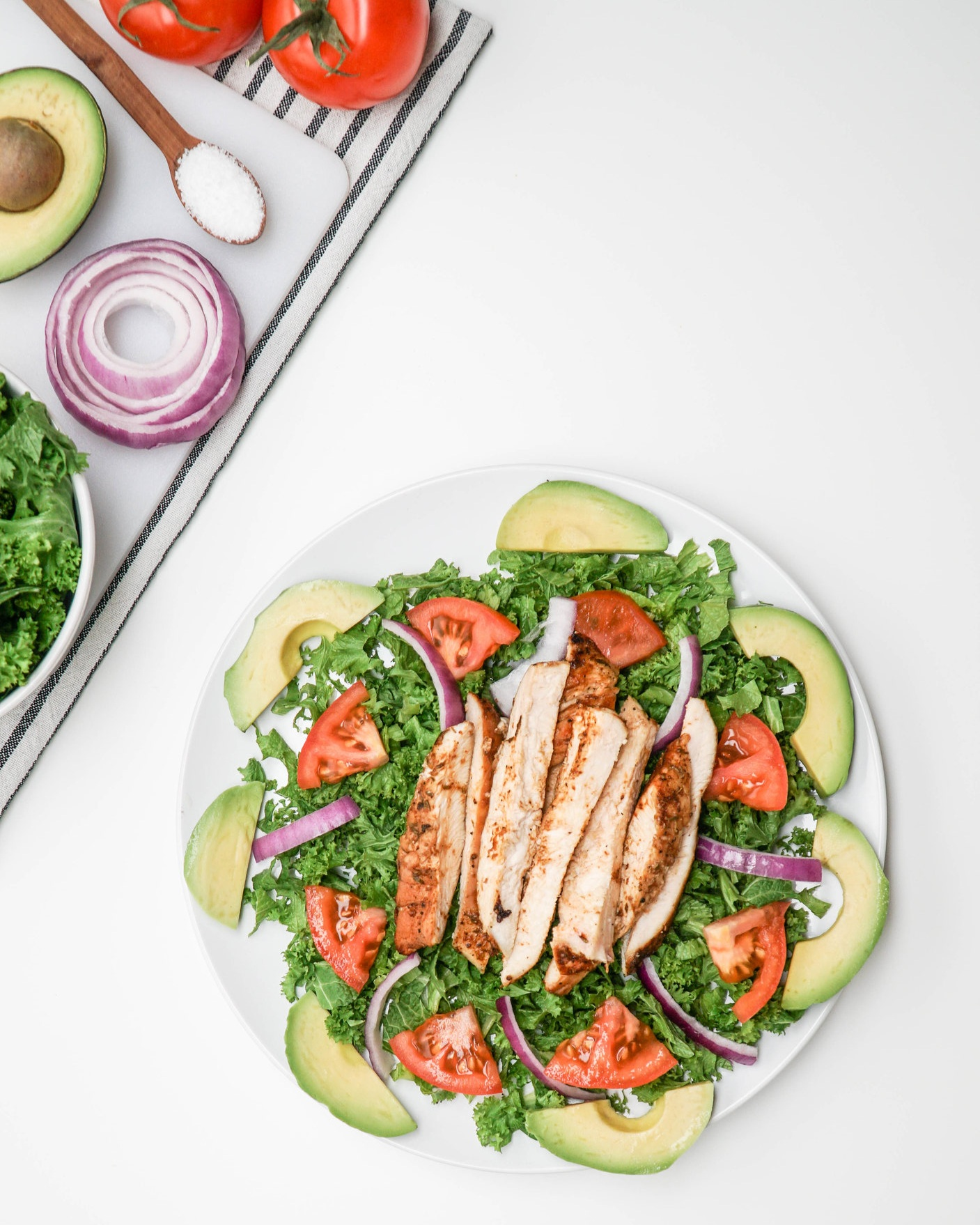 A plate of Cajun Chicken with Greens Avocado and Tomato Salad