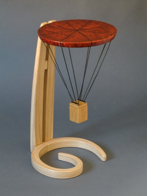 A small occasional table presented to a young man (initials G.H.) in recognition of his being awarded a hot air balloon pilot's license.  The 'gondola' will hold a small keepsake.   Ash, dyed curly maple, ebony.