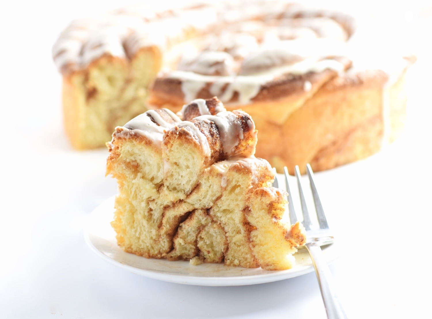 Cinnamon Roll Cake - soft, fluffy, gooey cinnamon rolls made easier and more beautiful in the form of a giant cinnamon roll cake! Must try! | trufflesandtrends.com