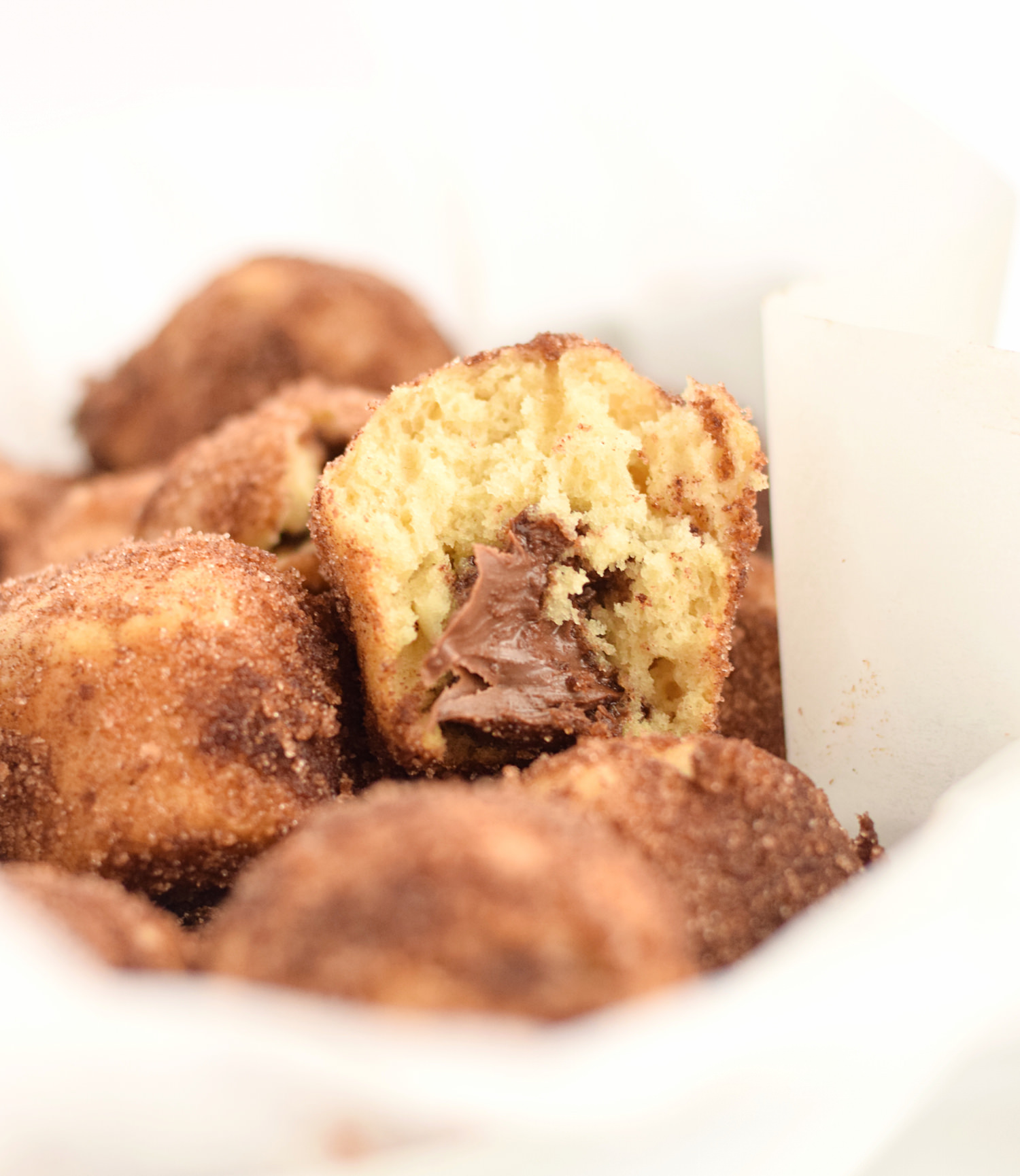 Nutella Churro Donut Muffins: soft, fluffy baked donuts dipped in melted butter, coated in cinnamon and sugar, and filled with Nutella! | TrufflesandTrends.com