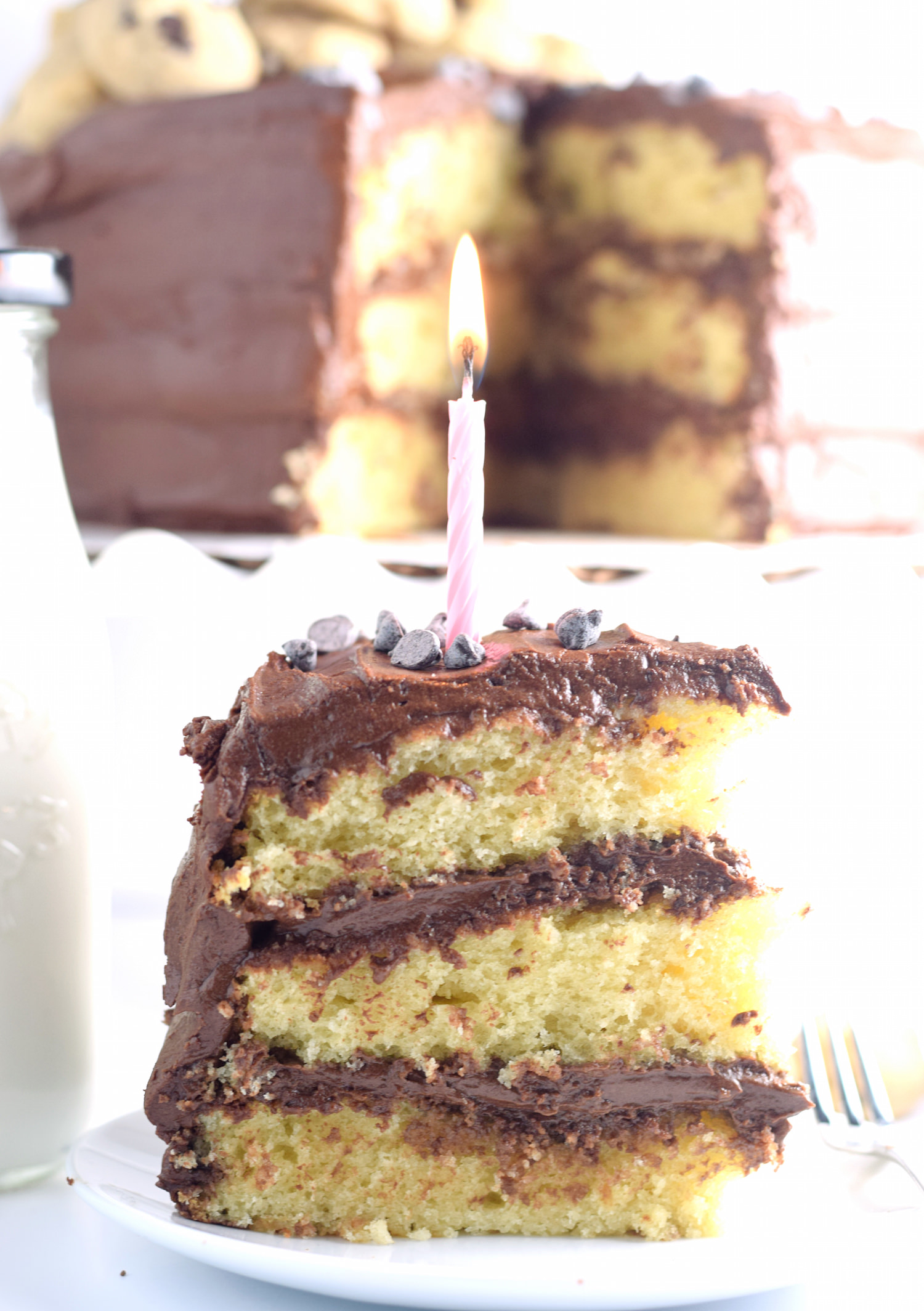 Yellow Layer Cake with Chocolate Buttercream Frosting: the best yellow cake filled with a decadent chocolate frosting and topped with mini chocolate chip cookies! | TrufflesandTrends.com