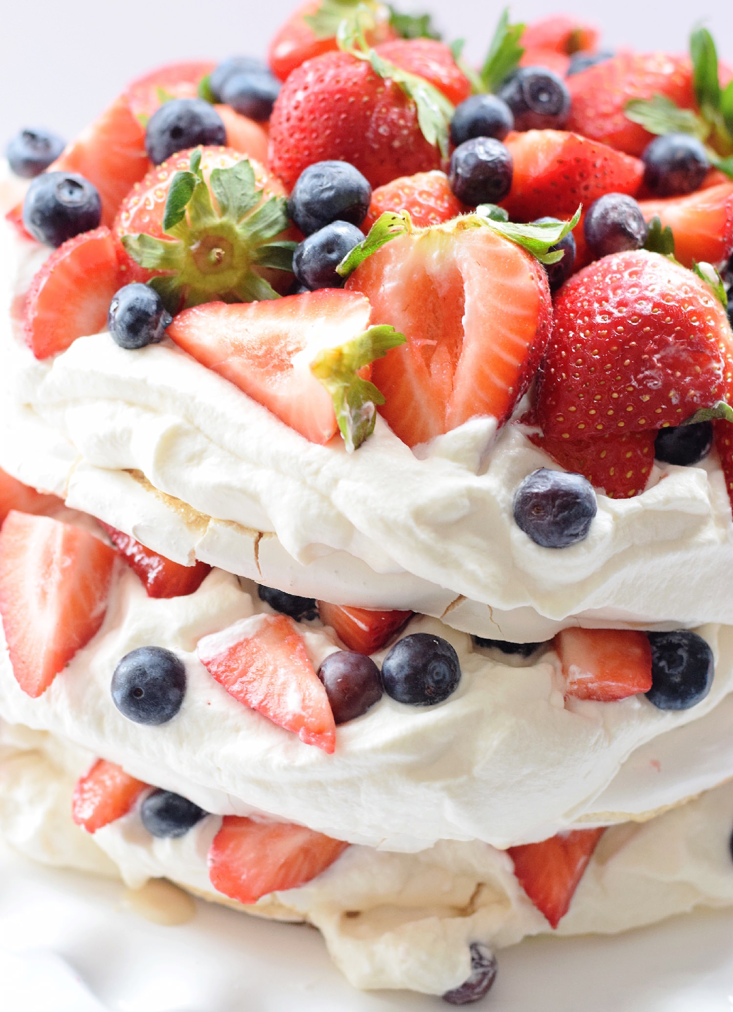 Mixed Berry Layer Pavlova Cake: chewy, sticky meringue layers filled with fresh whipped cream and assorted berries. Beautiful and gluten-free!