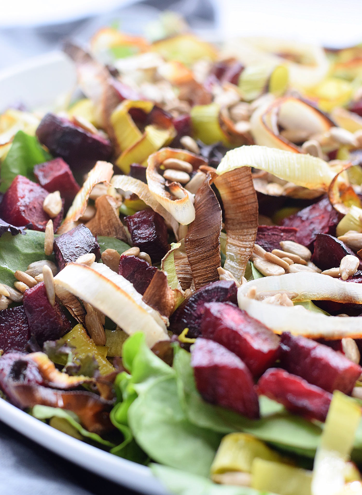 Roasted Leek and Beet Salad: mixed greens, roasted beets and leeks, sunflower seeds, and an olive oil-soy sauce dressing. So wholesome and delicious! | TrufflesandTrends.com