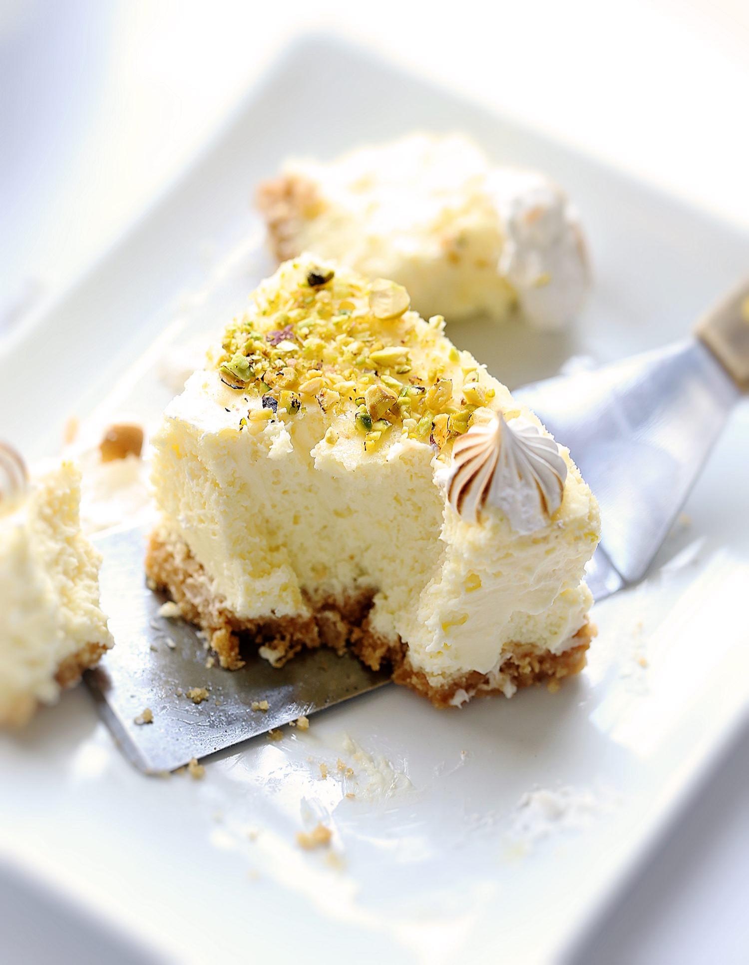 Creamy Lemon Meringue Cheesecake: buttery cookie crust, creamy, tart, spiked lemon filling, and sweet meringue topping. SO good! | TrufflesandTrends.com