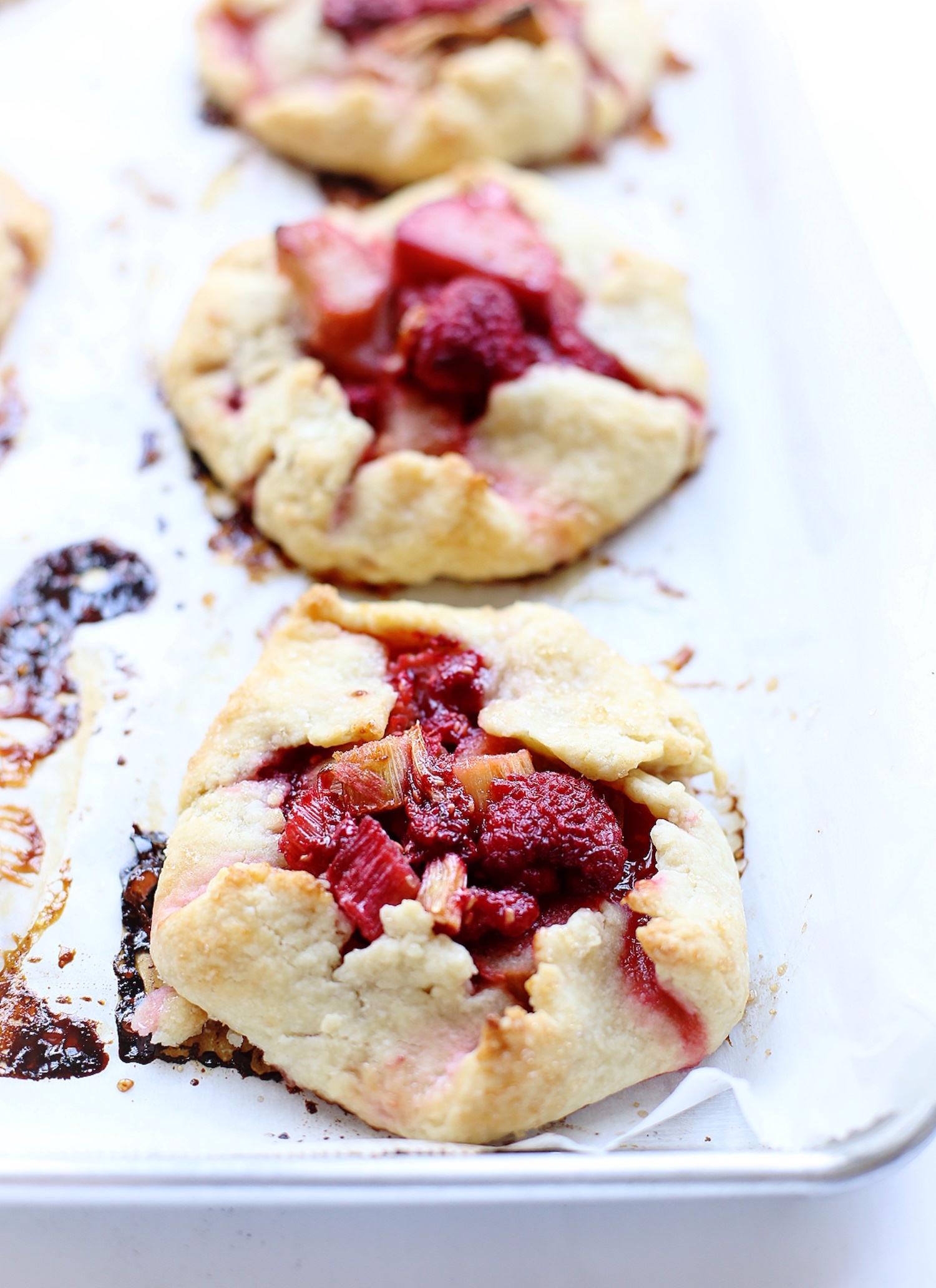 Mini Raspberry Rhubarb Galettes: amazing flaky, crispy crust with a tart raspberry-rhubarb filling. Perfect summer dessert! | TrufflesandTrends.com