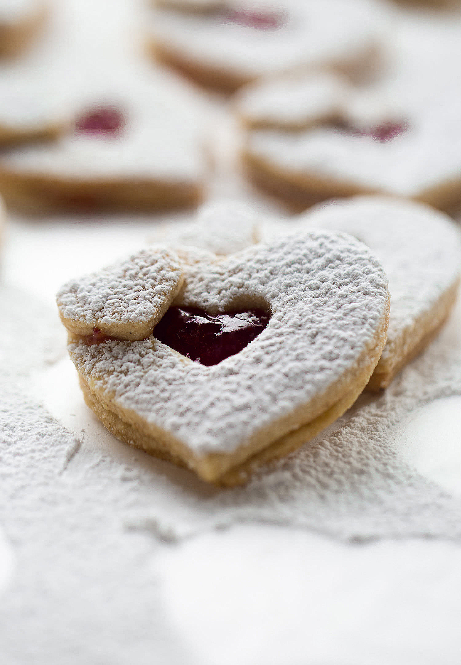 Spiced Linzer Heart Cookies: crispy, tender, buttery, spiced linzer cookies filled with raspberry jam. Perfect for Valentine's Day! | TrufflesandTrends.com