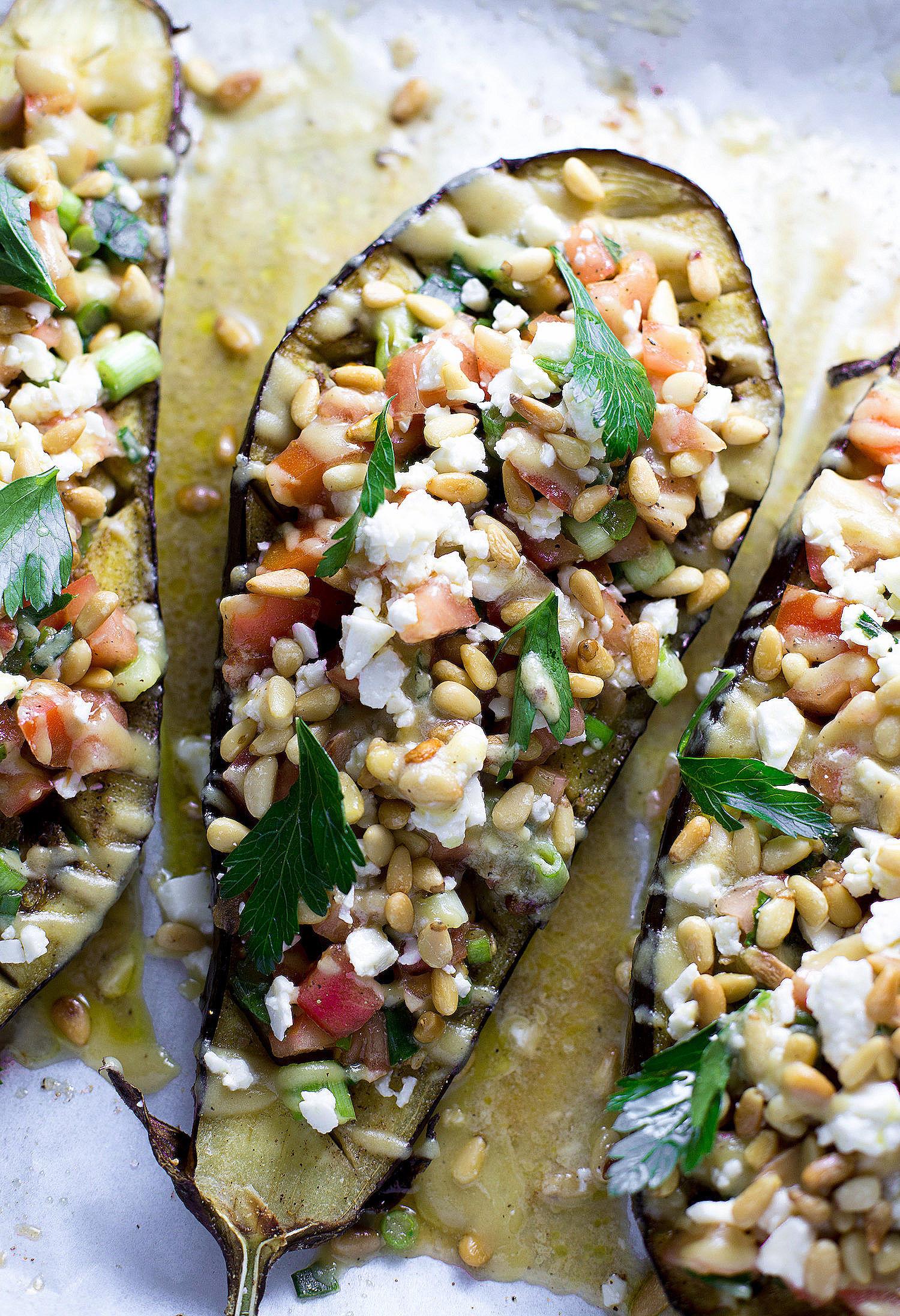 Roasted Eggplant with Tomatoes, Scallions, and Tahini: tender roasted eggplant halves with veggies, pine nuts, feta, and an addictive tahini dressing. | TrufflesandTrends.com