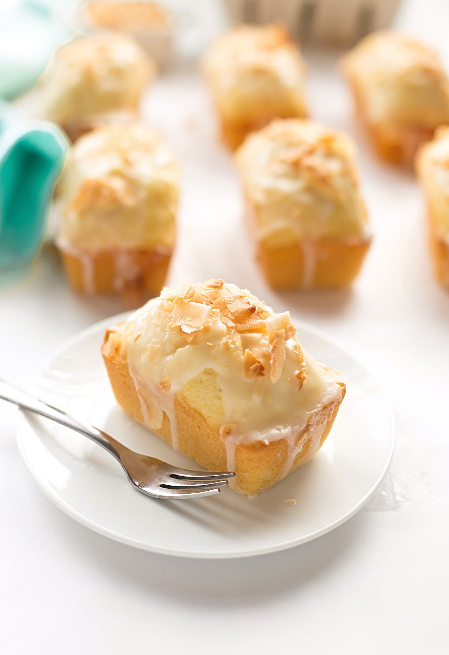 Mini Lemon Coconut Loaf Cakes: easy, soft, fluffy, loaf cakes full of lemon flavor and coconut flakes with a glossy, tangy glaze.   TrufflesandTrends.com