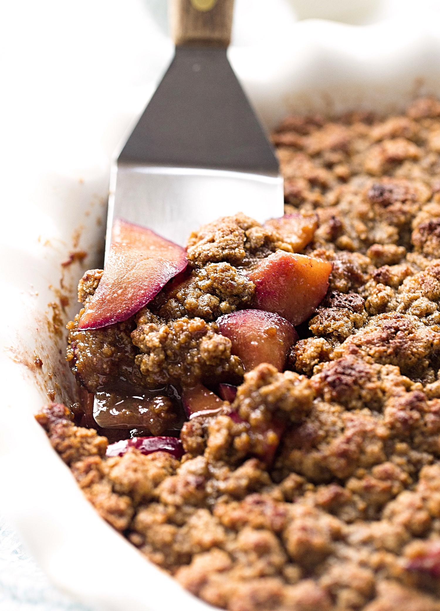 Gluten-Free Plum Tahini Crumble: tart, juicy plums topped with addictive, flourless tahini cookie crumbles. Dairy-free and delicious! | TrufflesandTrends.com