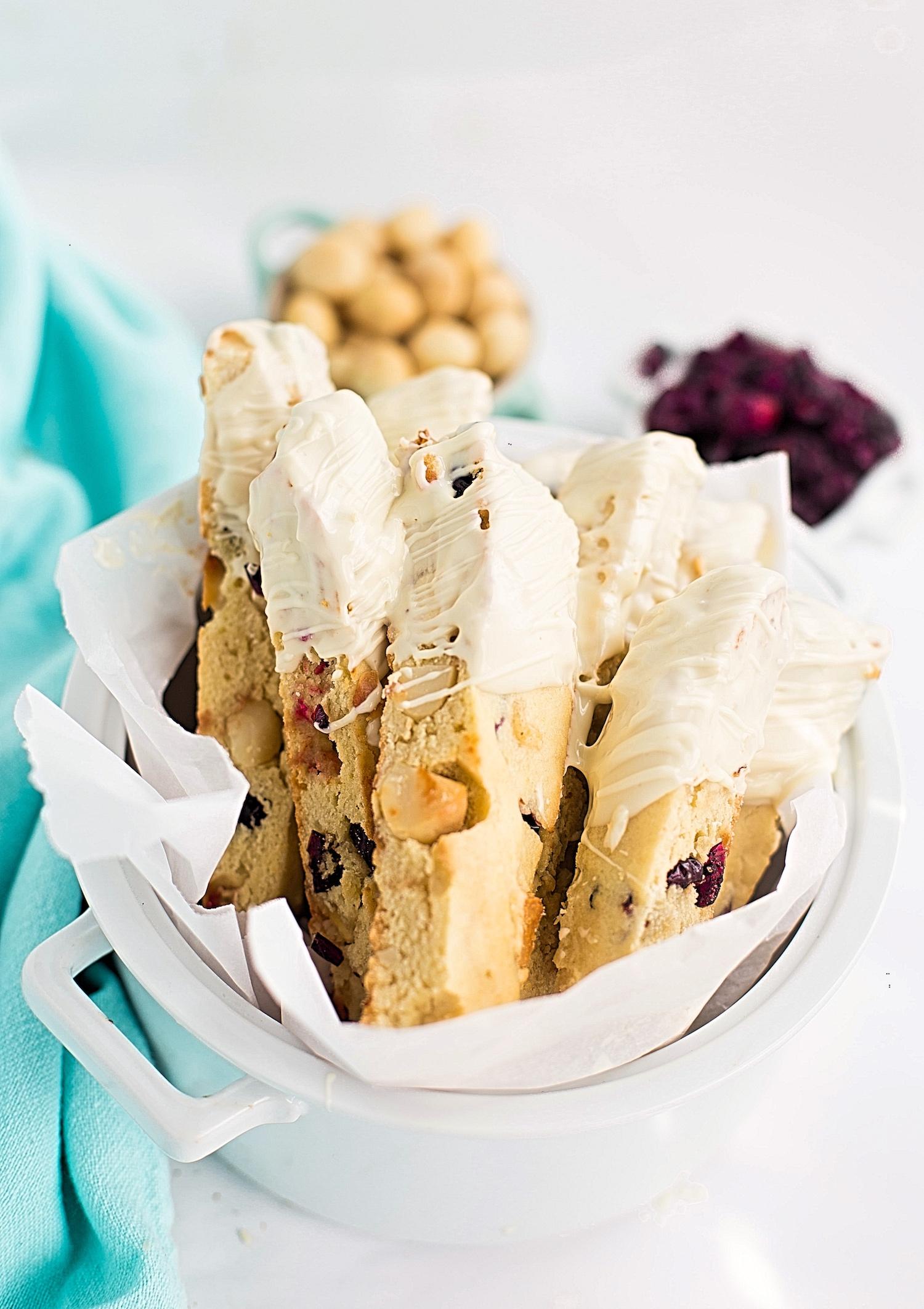 White Chocolate Cranberry Macadamia Biscotti: easy, tender biscotti full of white milk chocolate, dried cranberries, and macadamias. Video Included! | TrufflesandTrends.com