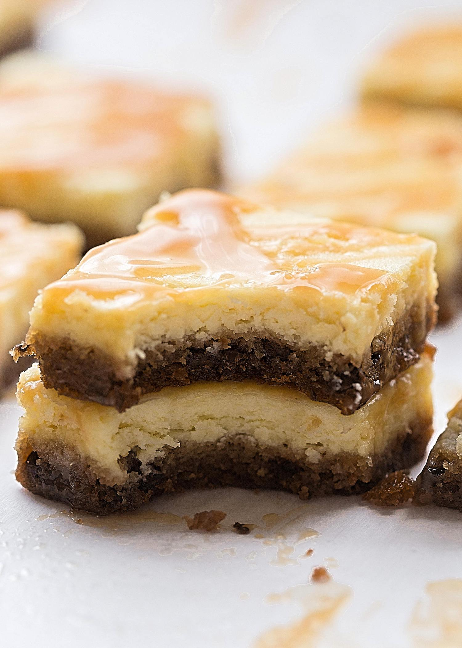 Salted Caramel Cheesecake Cookie Bars: gooey chocolate chip cookie dough topped with a classic, creamy cheesecake filling and a salted caramel drizzle. Easier than they look! | TrufflesandTrends.com