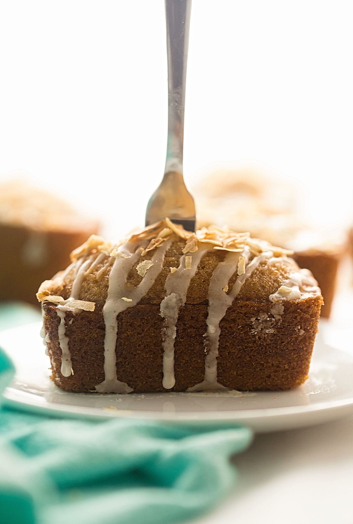 Mini Glazed Honey Loaf Cakes: soft, fluffy, perfectly spiced honey cakes drizzled with a cinnamon glaze and topped with toasted coconut flakes. Stays soft for weeks! | TrufflesandTrends.com
