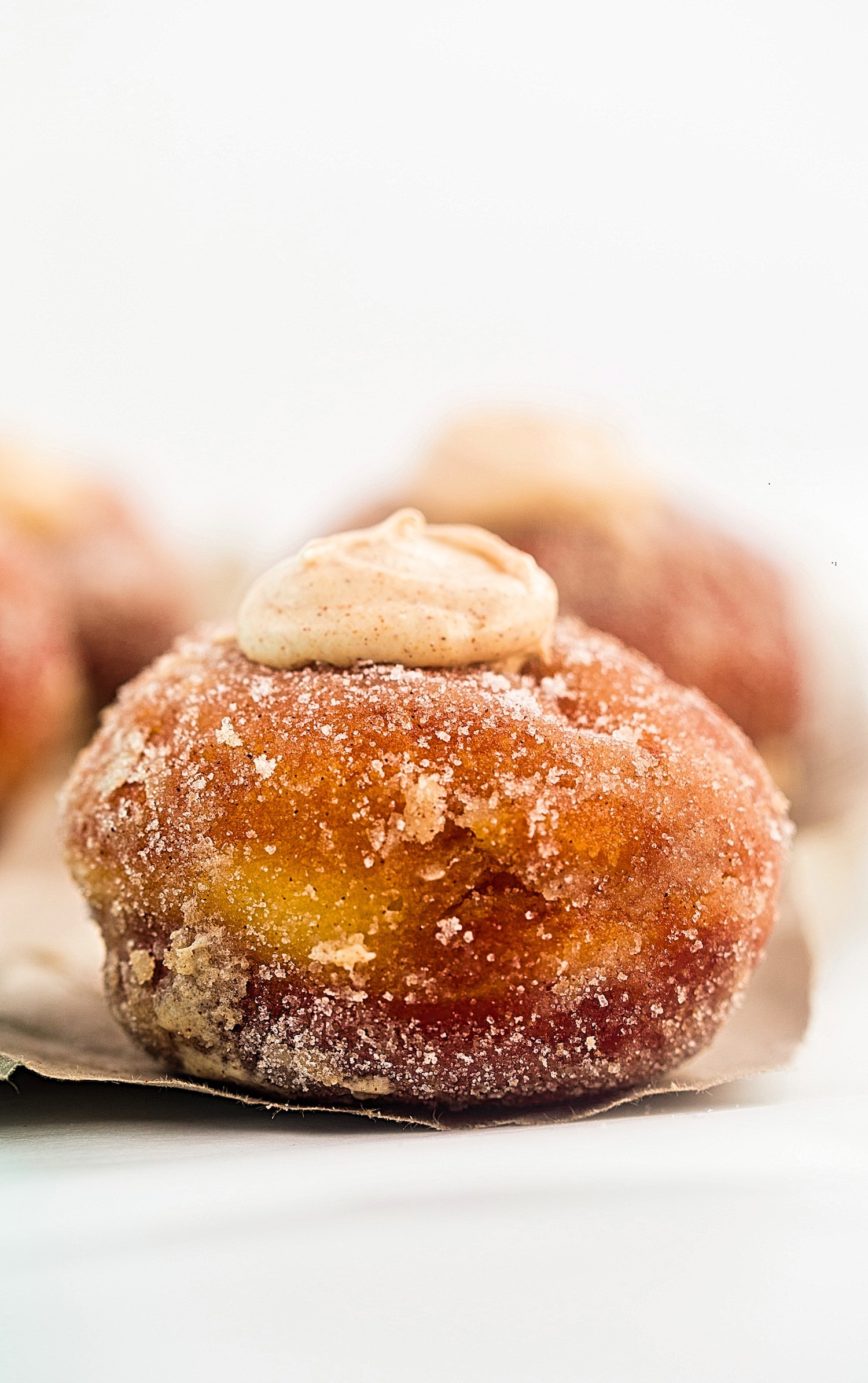 Fried Cinnamon Roll Donuts: perfect fried donuts filled with a cinnamon cheesecake filling before being rolled in hot butter and coated with a cinnamon, sugar mixture. | TrufflesandTrends.com