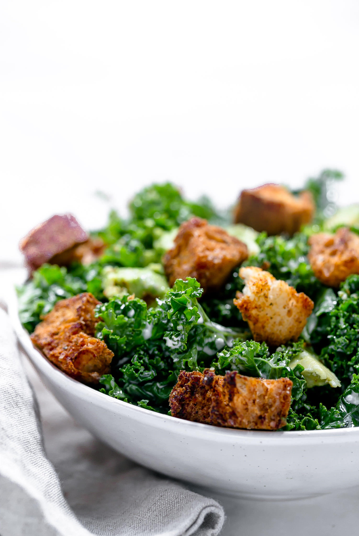 Garlicky Kale Avocado Salad With Homemade Croutons: crisp kale and creamy avocado tossed in a tangy, garlicky mayo dressing and topped with crunchy homemade croutons. | TrufflesandTrends.com