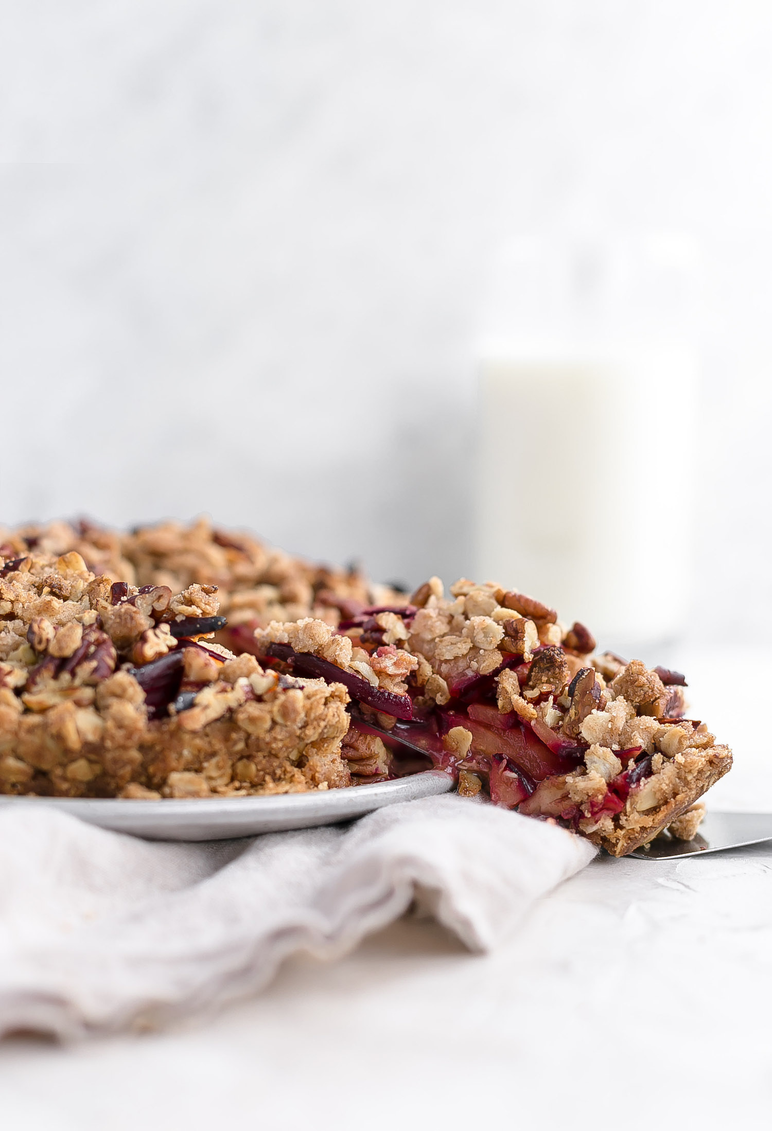 Whole Wheat Plum Pecan Oat Crumble Tart: crispy, crunchy oat crust topped with a juicy plum filling and sprinkled with a pecan oat crumble. Dairy-free! | TrufflesandTrends.com