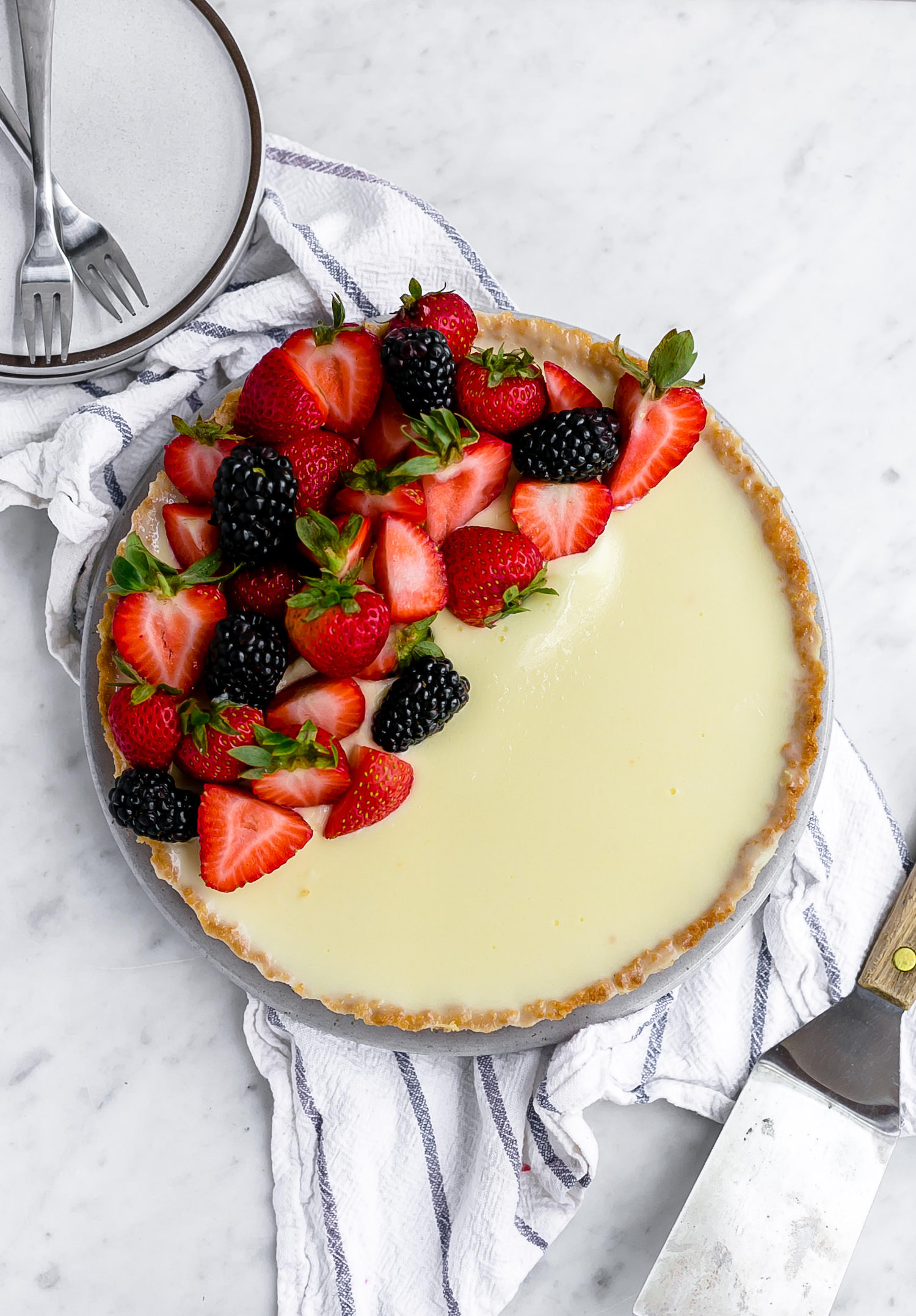 Easy Cookie Crust Lemon Tart: tender, crumbly cookie base filled with a creamy, rich, tangy lemon filling and a garnish of fresh berries. Easy and decadent! | TrufflesandTrends.com