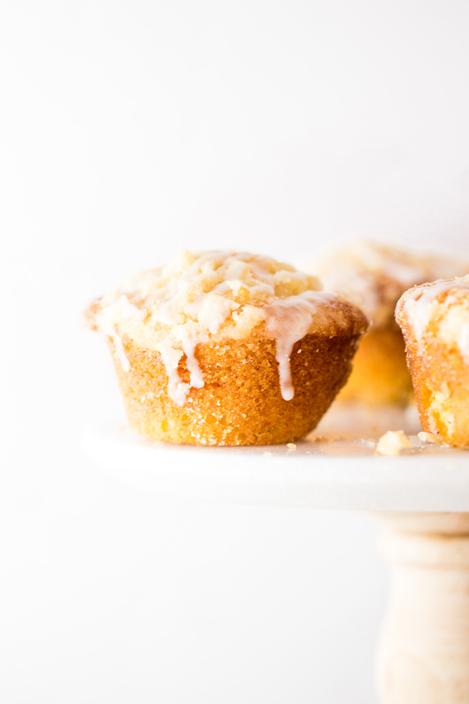 Peaches and Cream Muffins: soft, moist, fluffy, filled with juicy peaches, generously topped with crumble, and drizzled with a sweet glaze. Dairy-free! | TrufflesandTrends.com