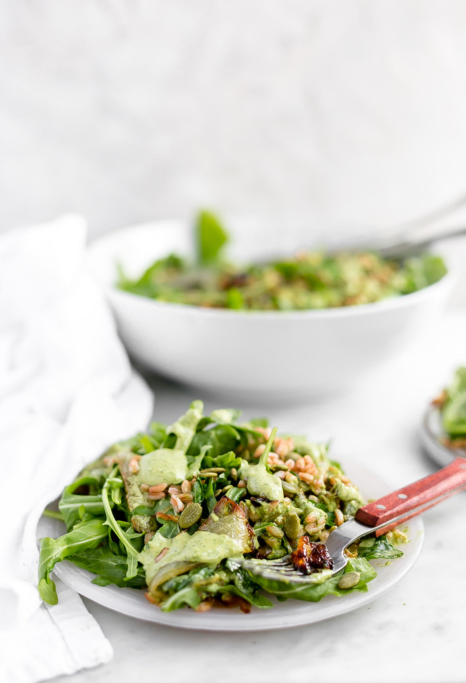 Arugula Farro Caramelized Onion Salad with Green Tahini: fresh arugula, hearty farro, sweet caramelized onions, toasted pumpkin seeds, and a delicious lemon-parsley-tahini dressing. | TrufflesandTrends.com