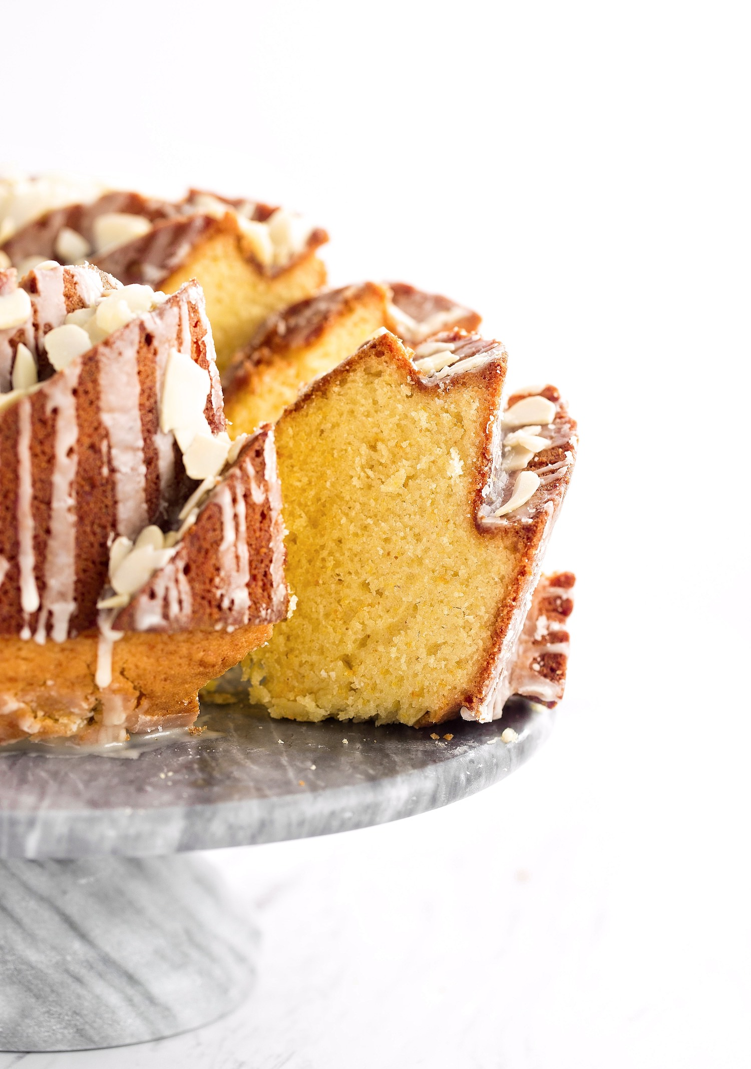 Glazed Orange Almond Bundt Cake: easy, moist, fluffy, and packed with flavor from orange zest, freshly squeezed orange juice, almond extract, and an orange glaze and sliced almond garnish. | TrufflesandTrends.com