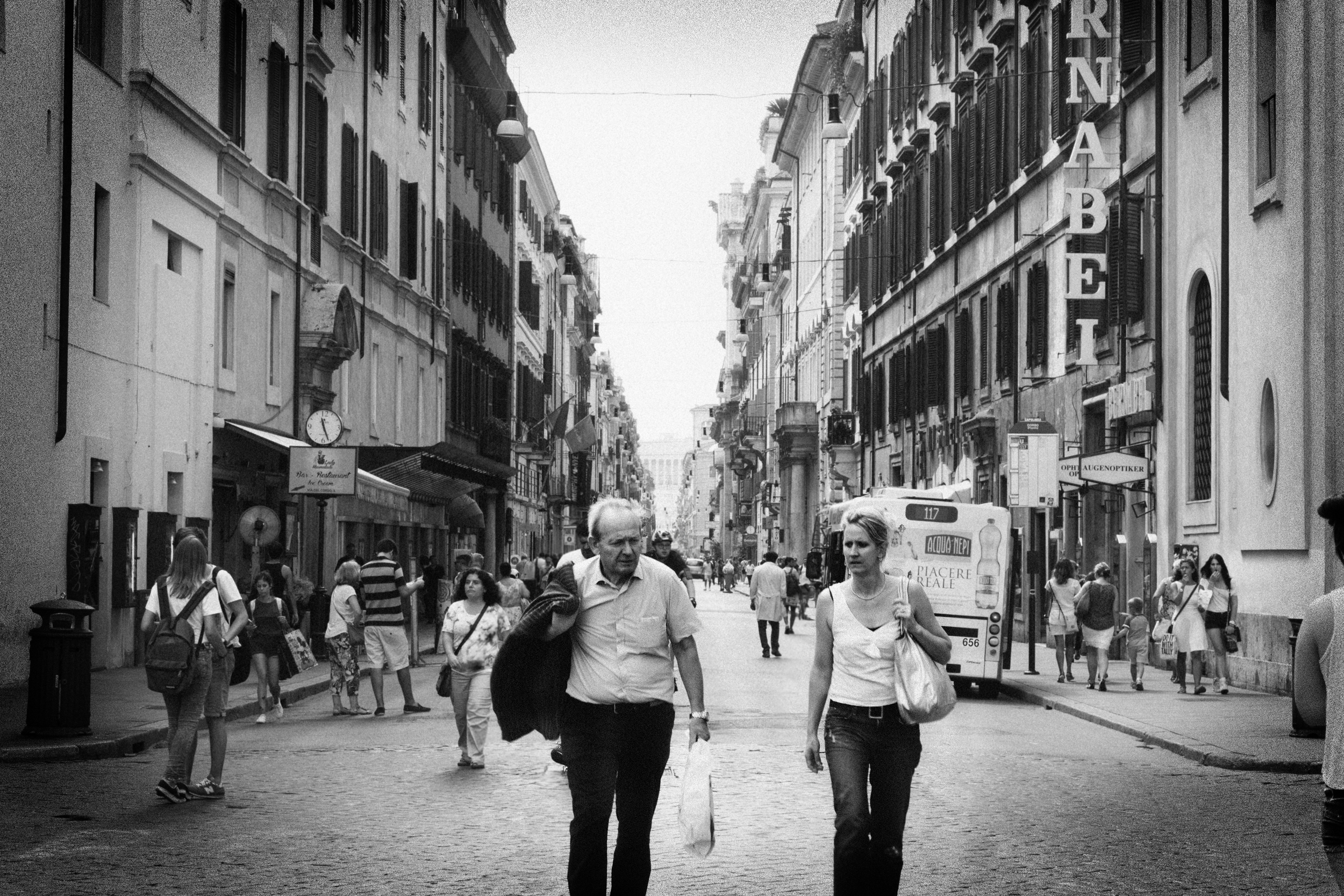 Two people leaving Via del Corso heading toward Piazza de Popolo in the Tridente neighborhood.