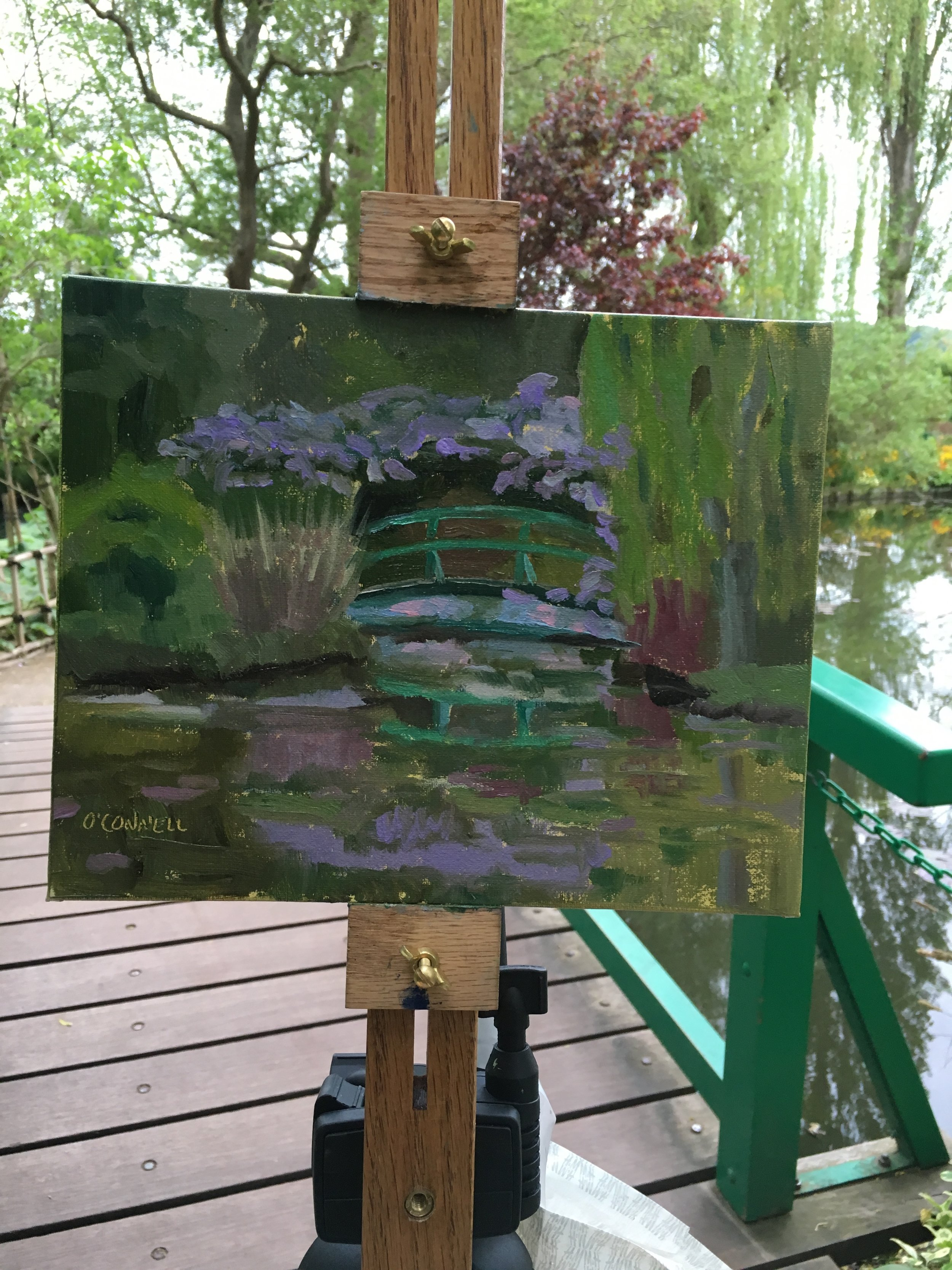 Painting in progress of wisteria in bloom on the bridge