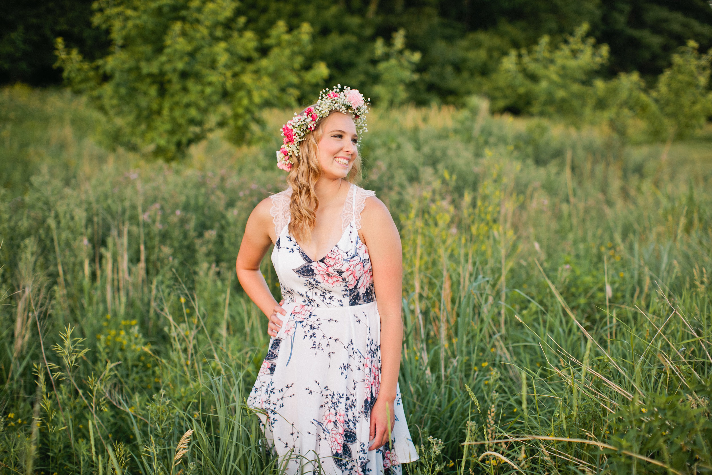 girl smiling in flower crown and dress for senior photos