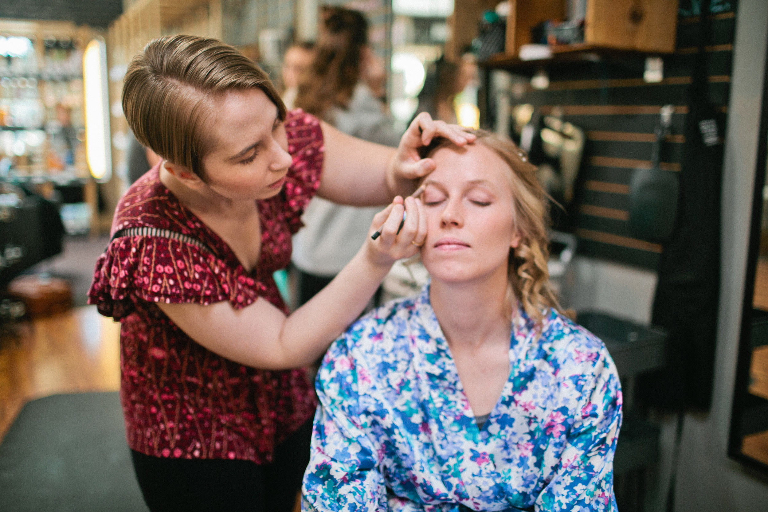 older sister helping bride with makeup on wedding day